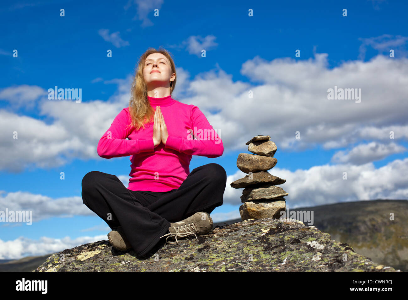 Young woman relaxing on mountains. - Stock Image