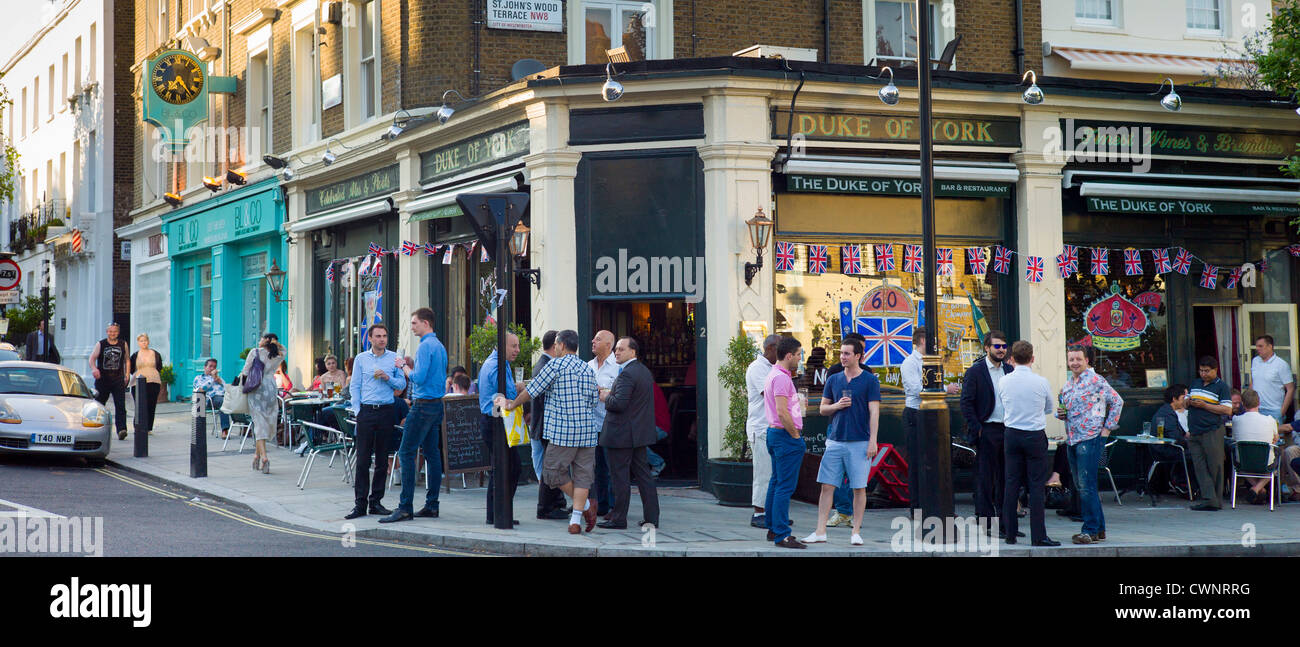 Customers enjoying warm weather at The DUKe of York traditional London pub in St John's Wood, London - Stock Image