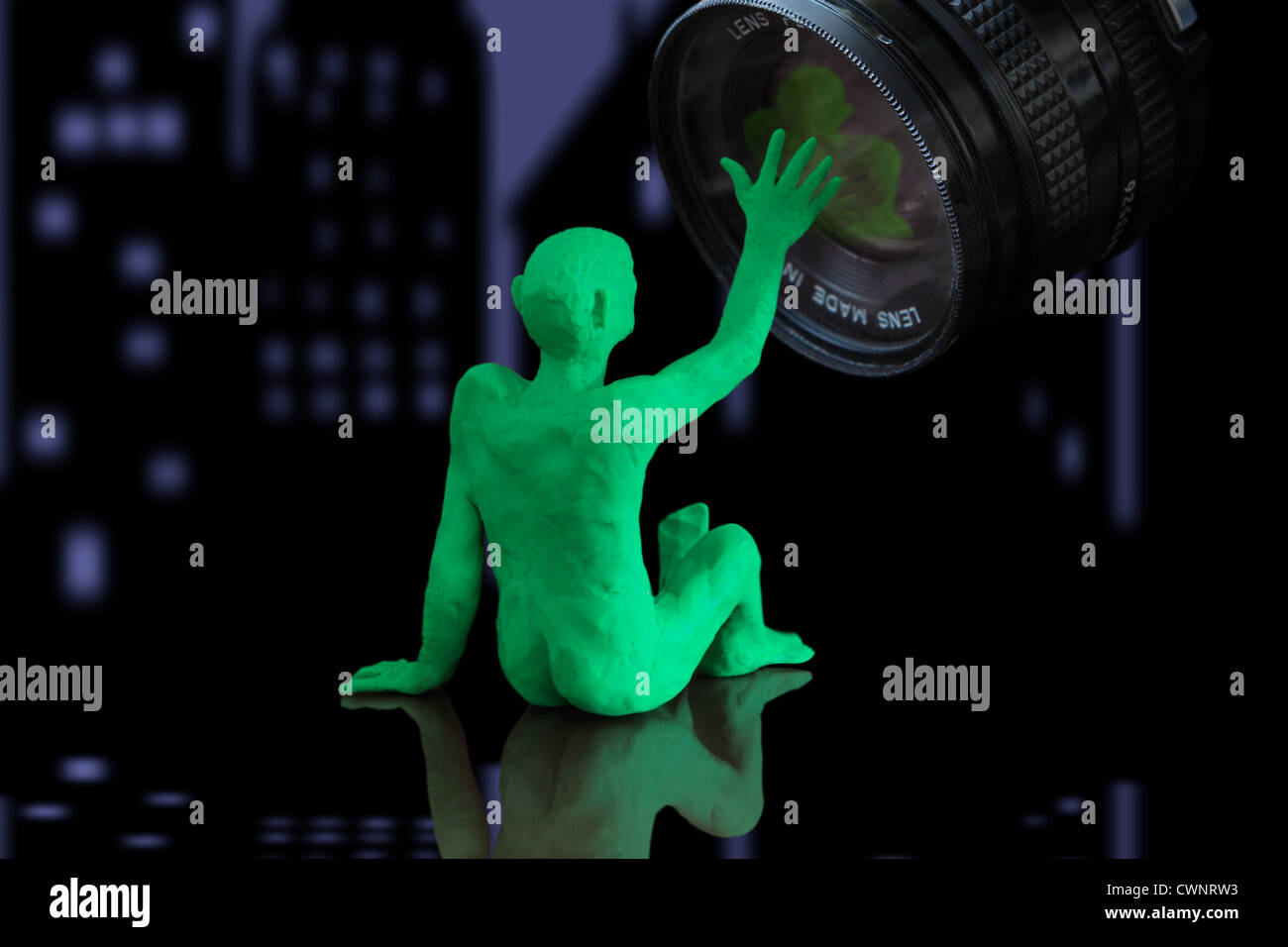 we see a figurine that represents a person sitting down and interacting with a camera lens. City at night in background - Stock Image
