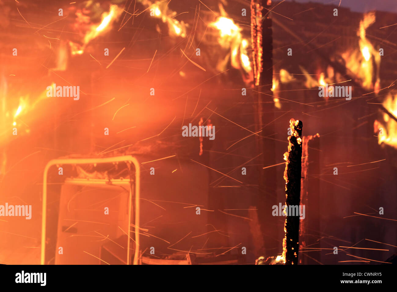 House interior destroyed by intense fire. Flames, smoke and sparks engulfing the interior of a home. - Stock Image