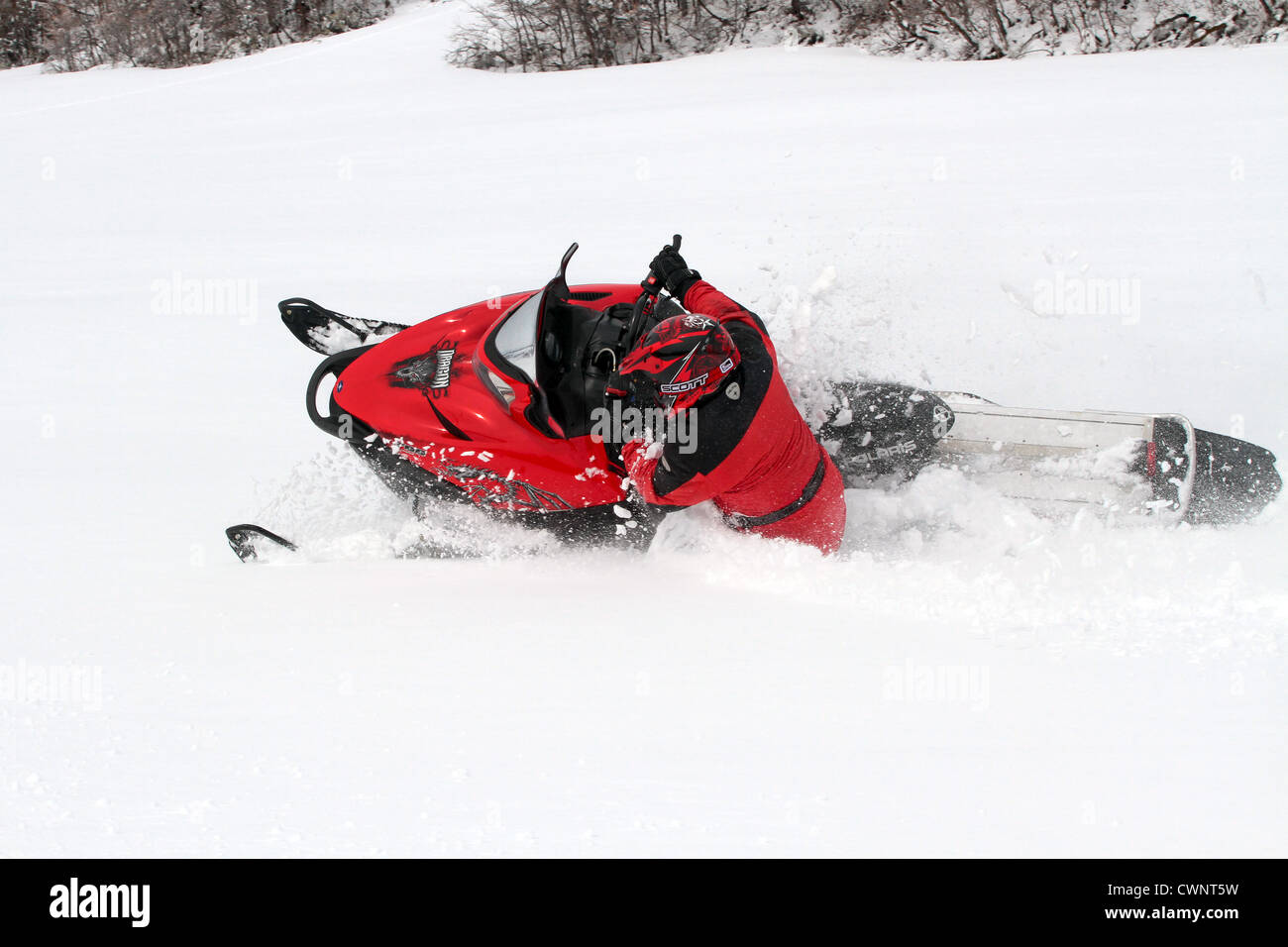 Snowmobile rider having fun and turning in fresh white snow. Sharp turns in a high altitude mountain meadow. - Stock Image