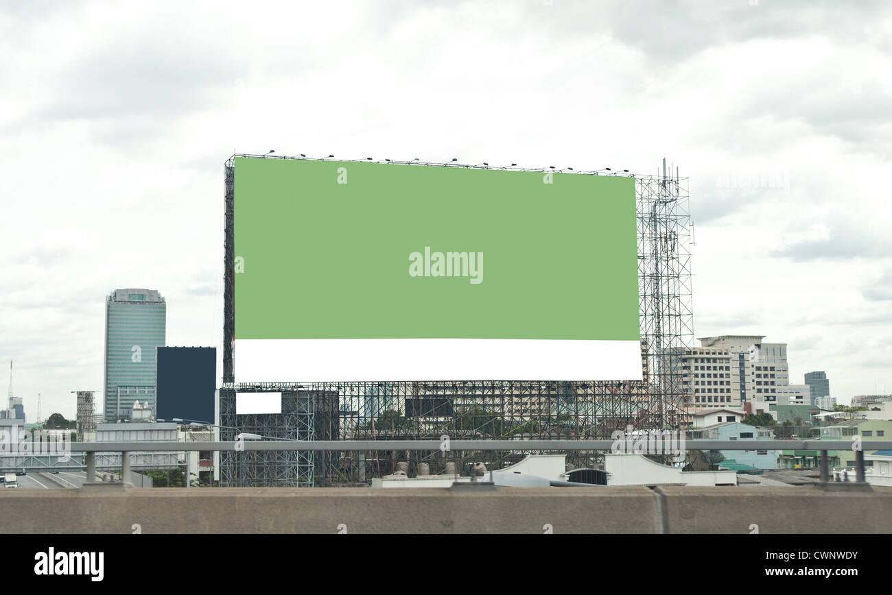 green empty billboard on city. - Stock Image