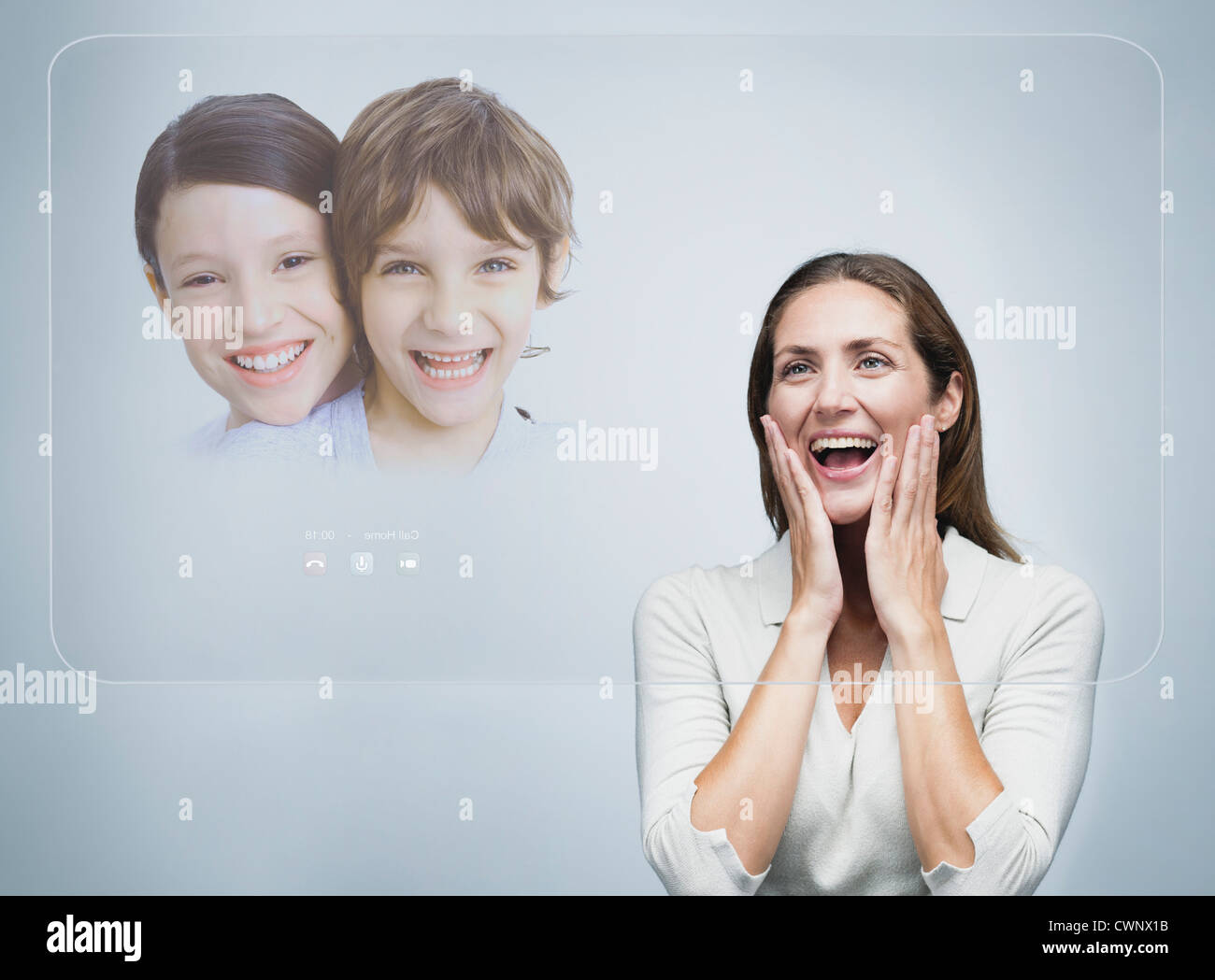 Woman doing video conference with children using advanced touch screen technology - Stock Image