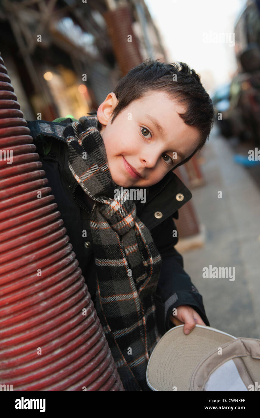 Boy peering around column at camera, portrait - Stock Image