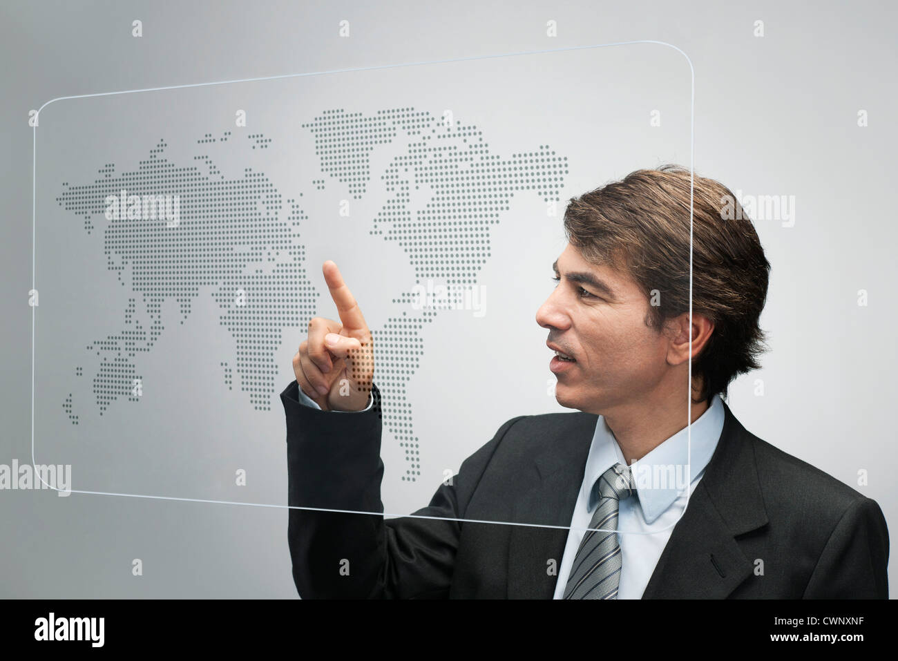 Businessman using advanced touch screen technology to view world map - Stock Image