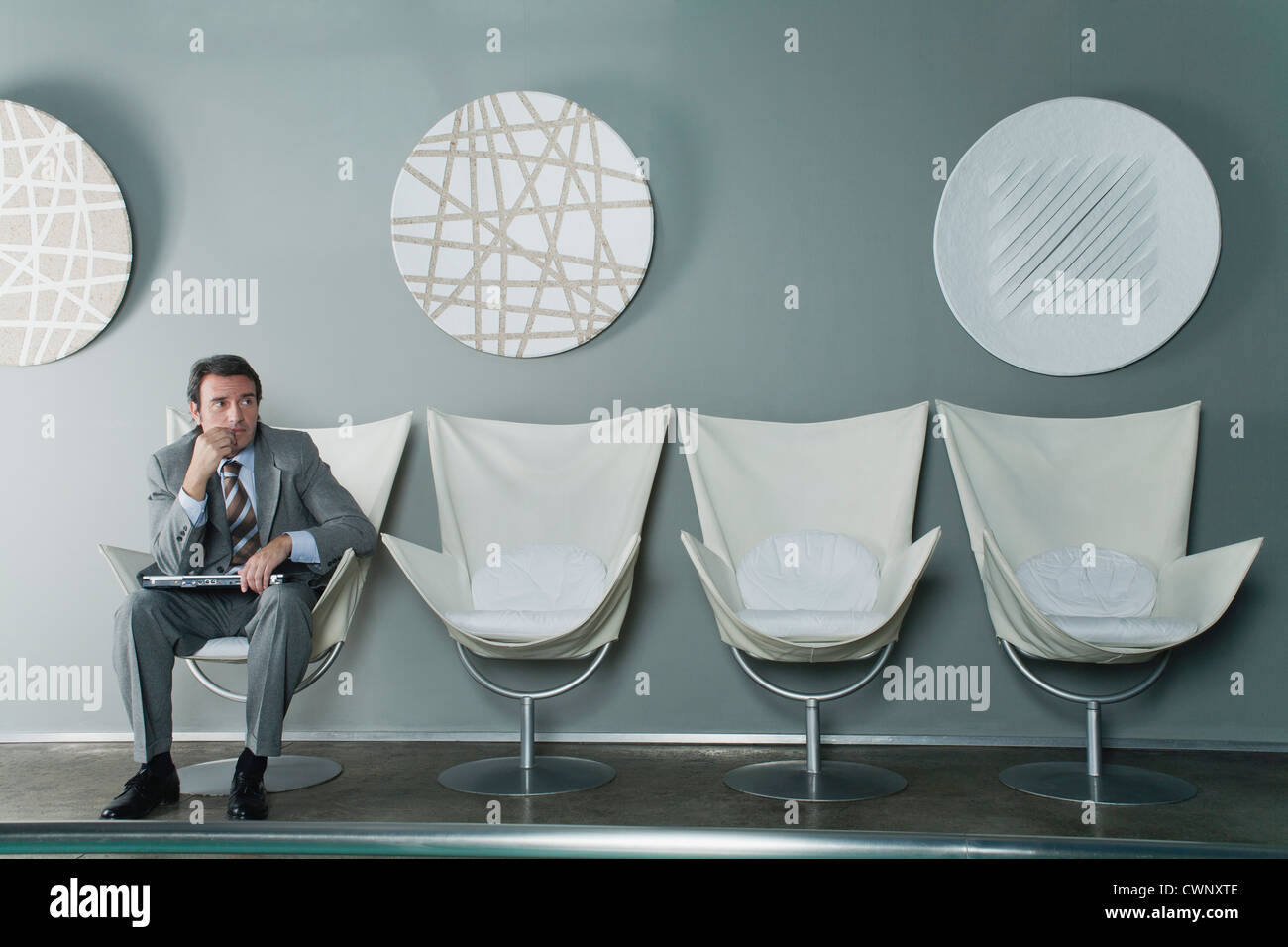 Mature businessman sitting at end of row of chairs in waiting room - Stock Image