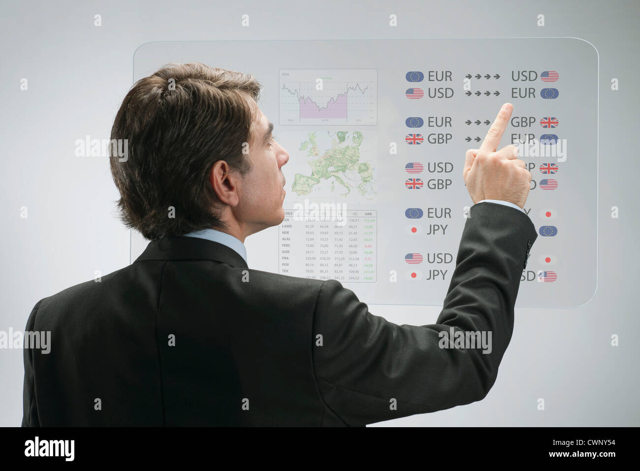 Businessman using advanced touch screen technology to view business data - Stock Image
