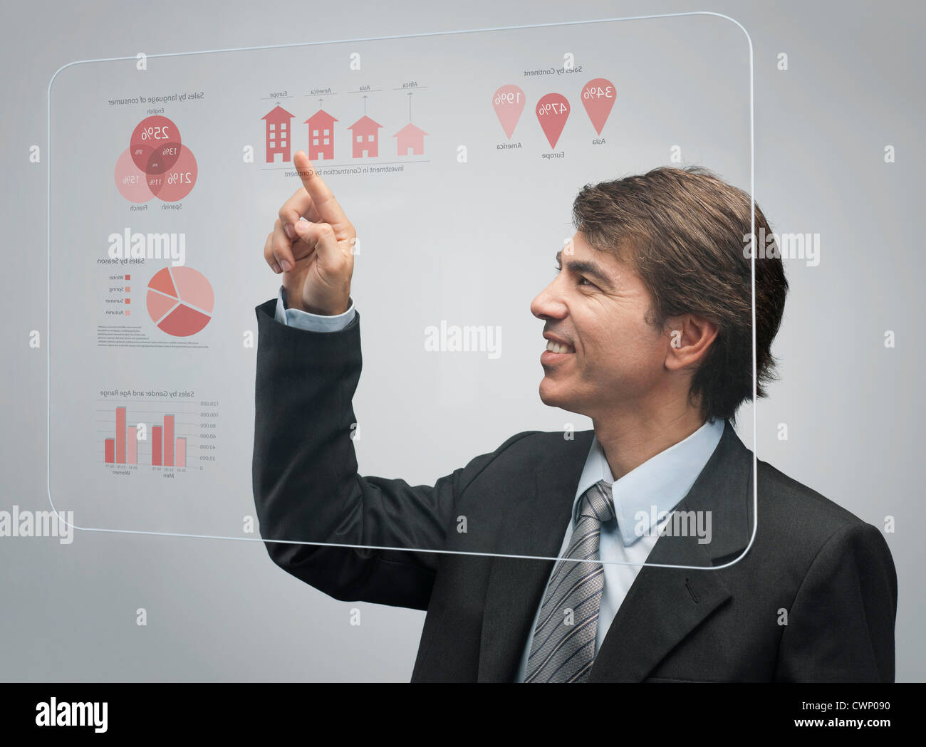 Businessman using advanced touch screen technology to view sales data - Stock Image