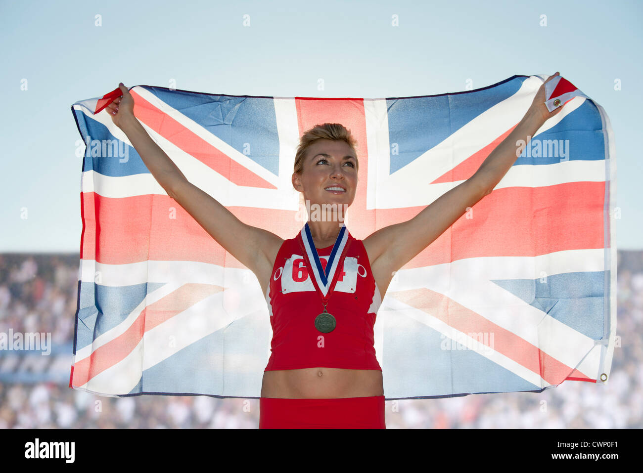 Young female medalist holding up British flag - Stock Image