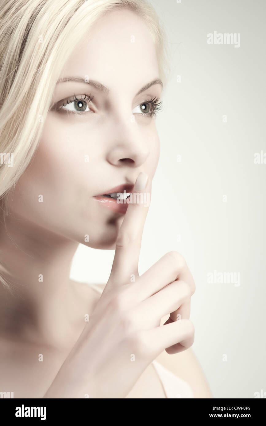 Young woman with finger on lips - Stock Image