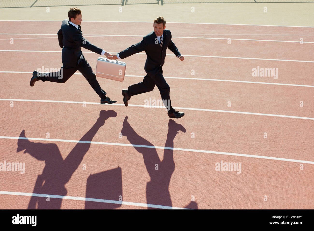 Businessmen passing briefcase while running on running track - Stock Image