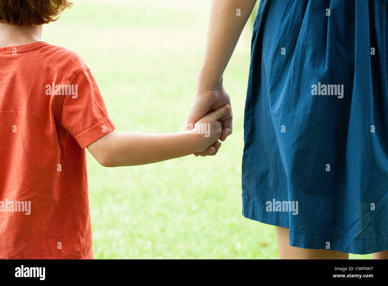 Boy holding mother's hand, rear view - Stock Image