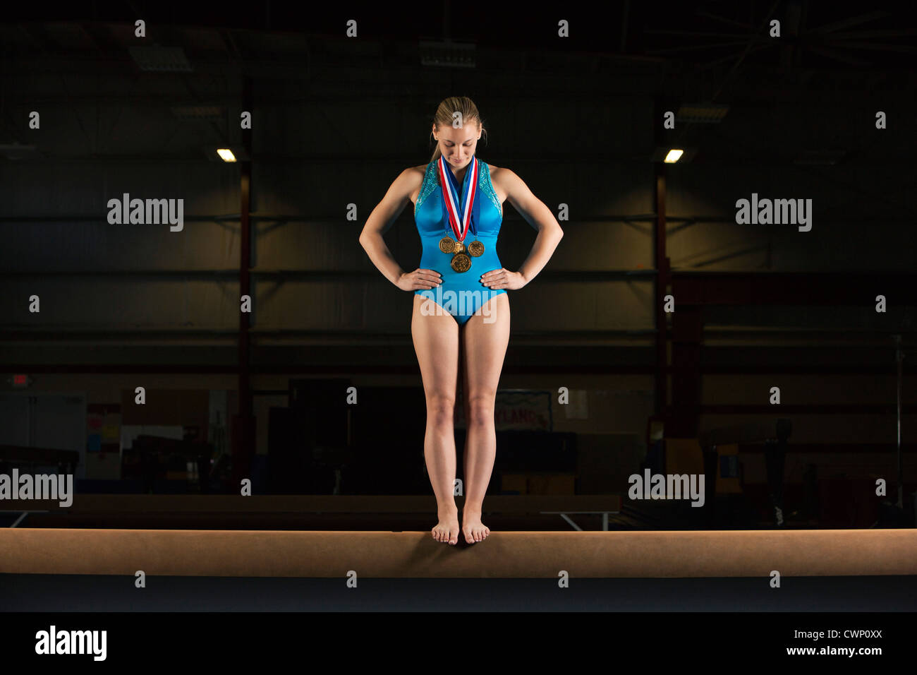 Gymnast with medals standing on balance beam - Stock Image