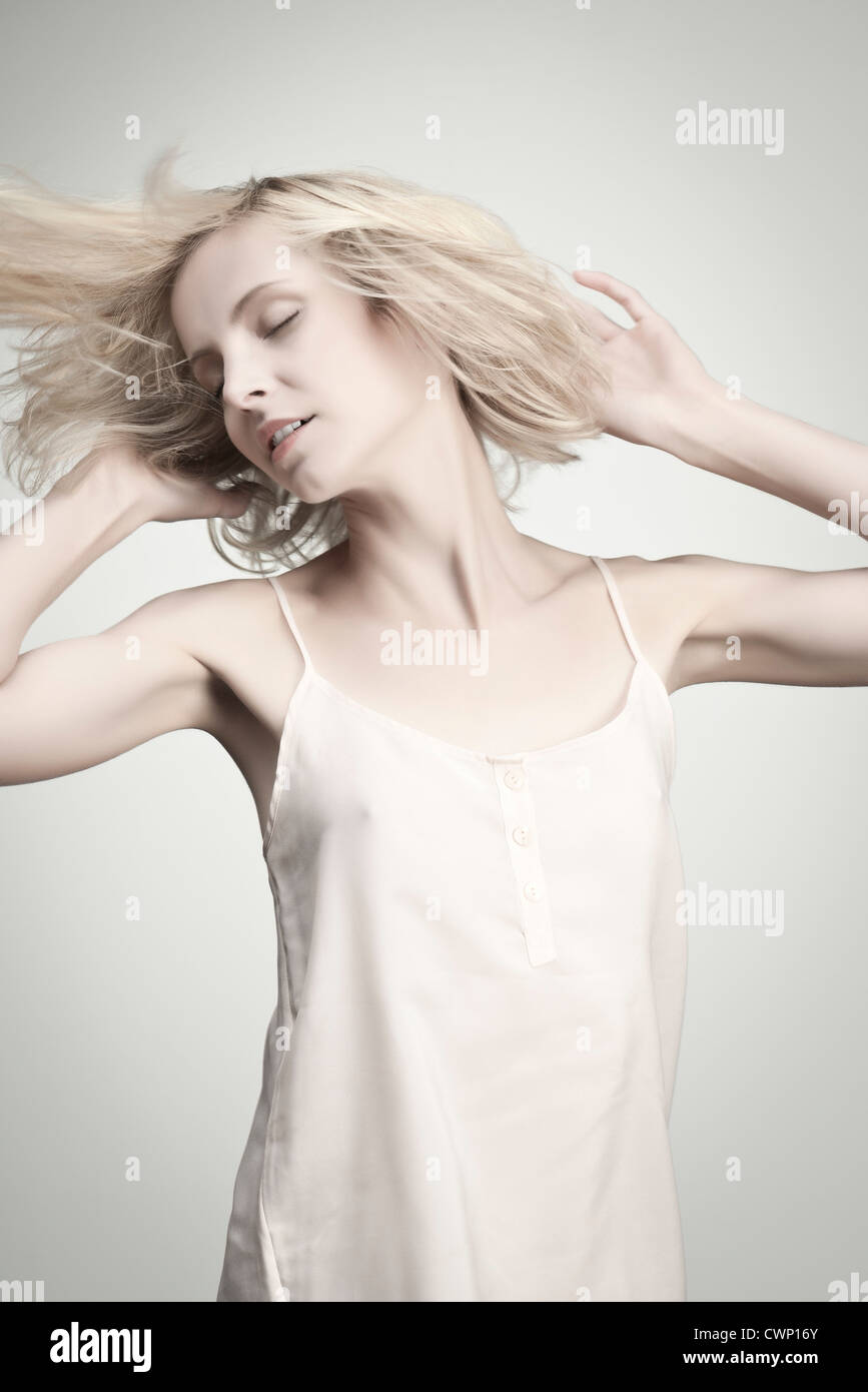 Young woman tossing hair with eyes closed, portrait - Stock Image