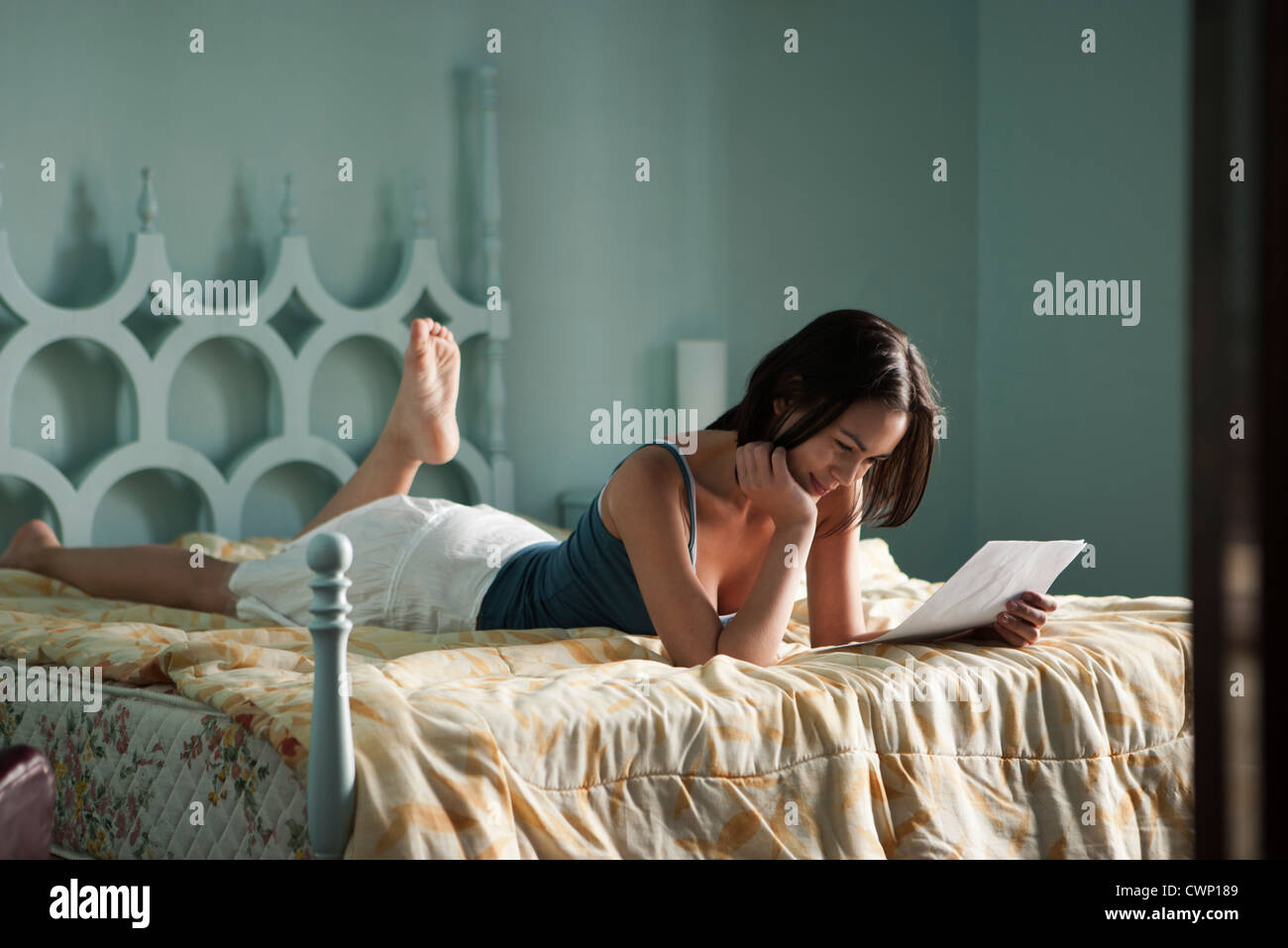 Woman lying on bed, reading letter - Stock Image