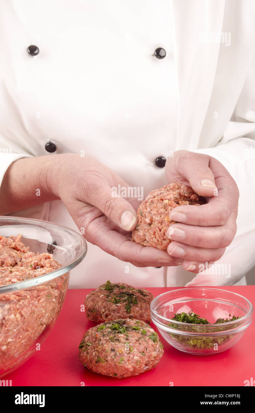 female chef preparing meat balls with herbs - Stock Image
