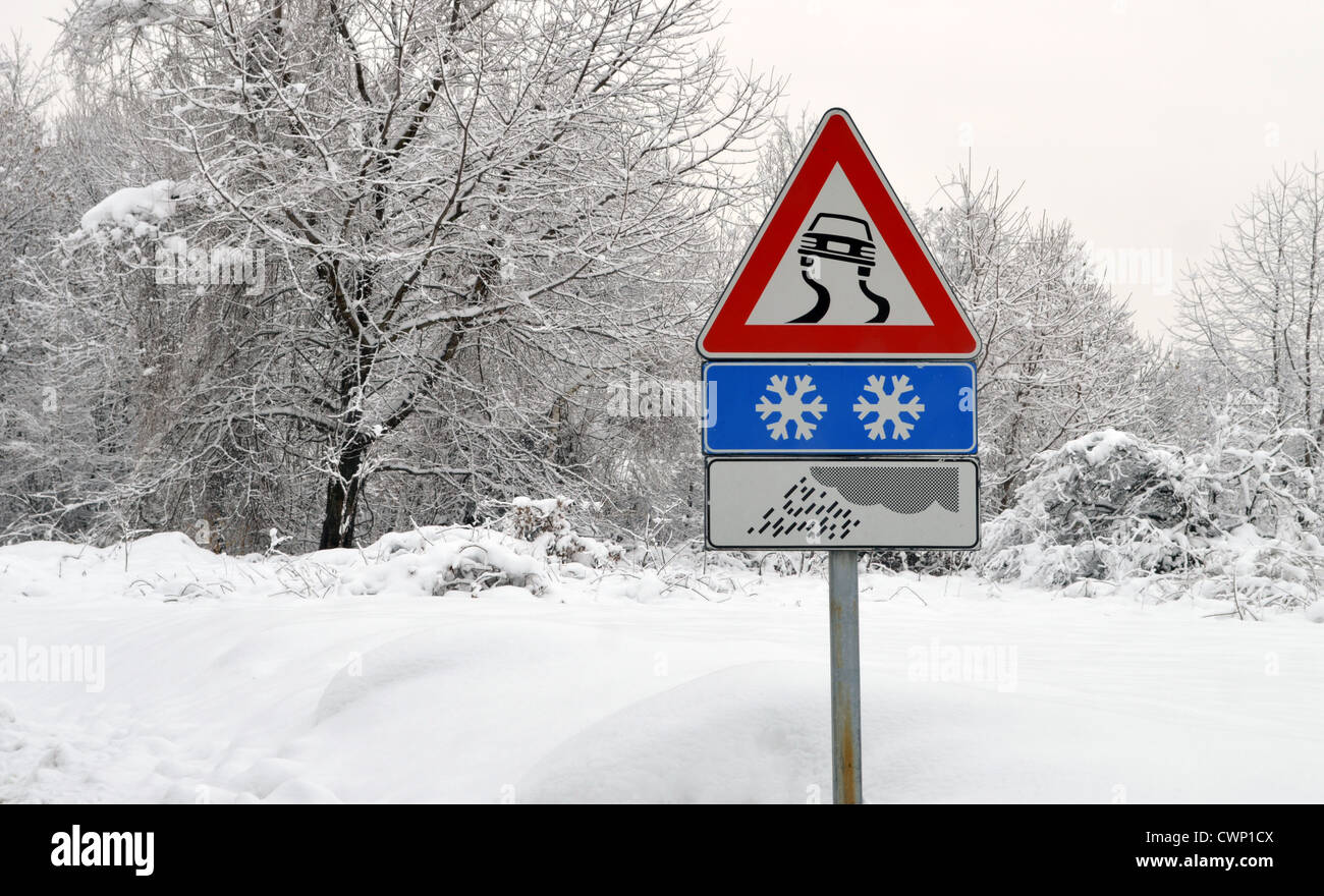 Slippery road sign in snow. Severe weather conditions - Stock Image