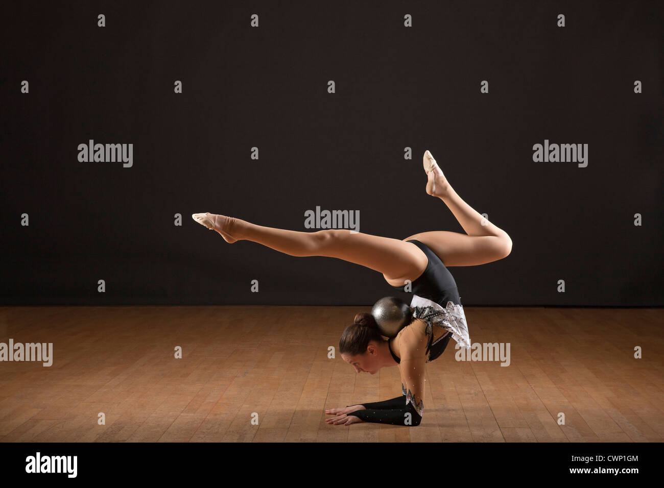 Gymnast bending backwards, balancing ball with head - Stock Image