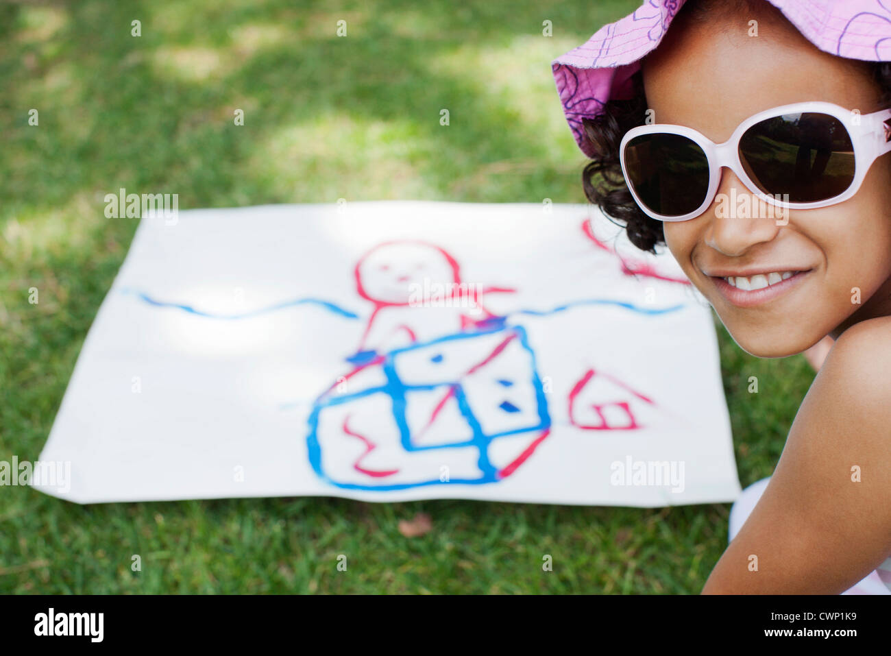 Girl with drawing on grass - Stock Image