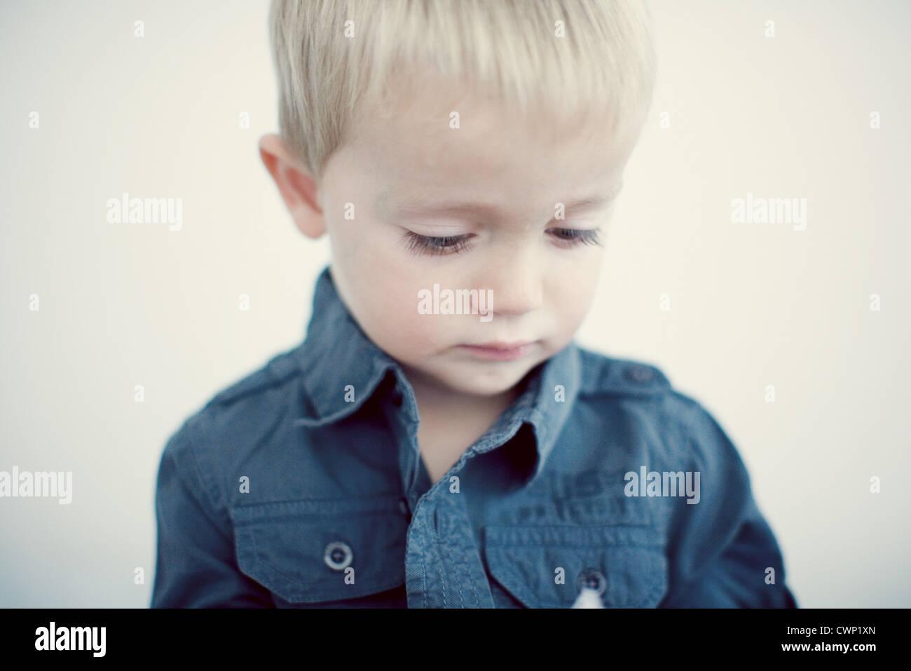 Little boy looking down, portrait - Stock Image