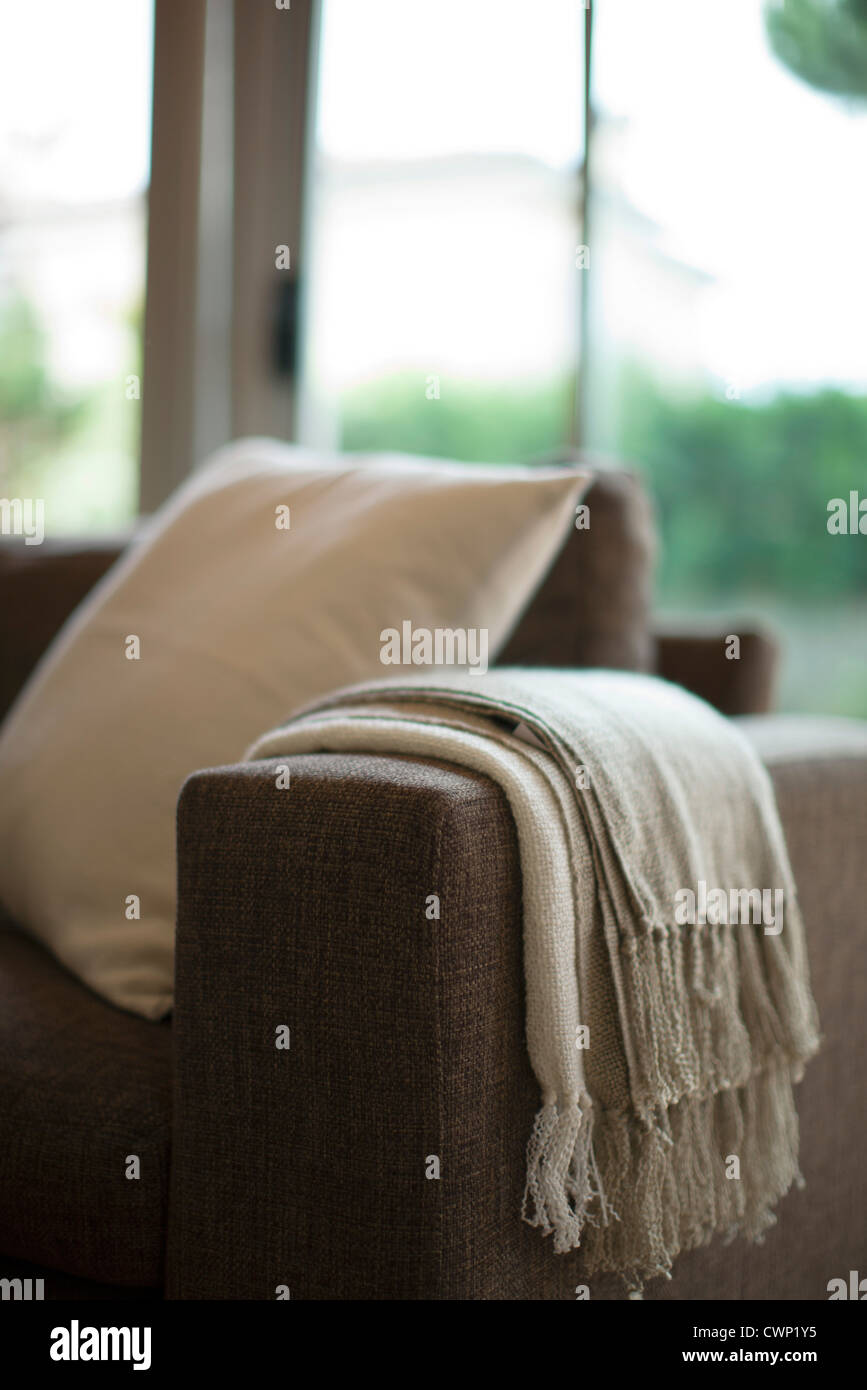 Blanket and cushion on sofa, cropped - Stock Image