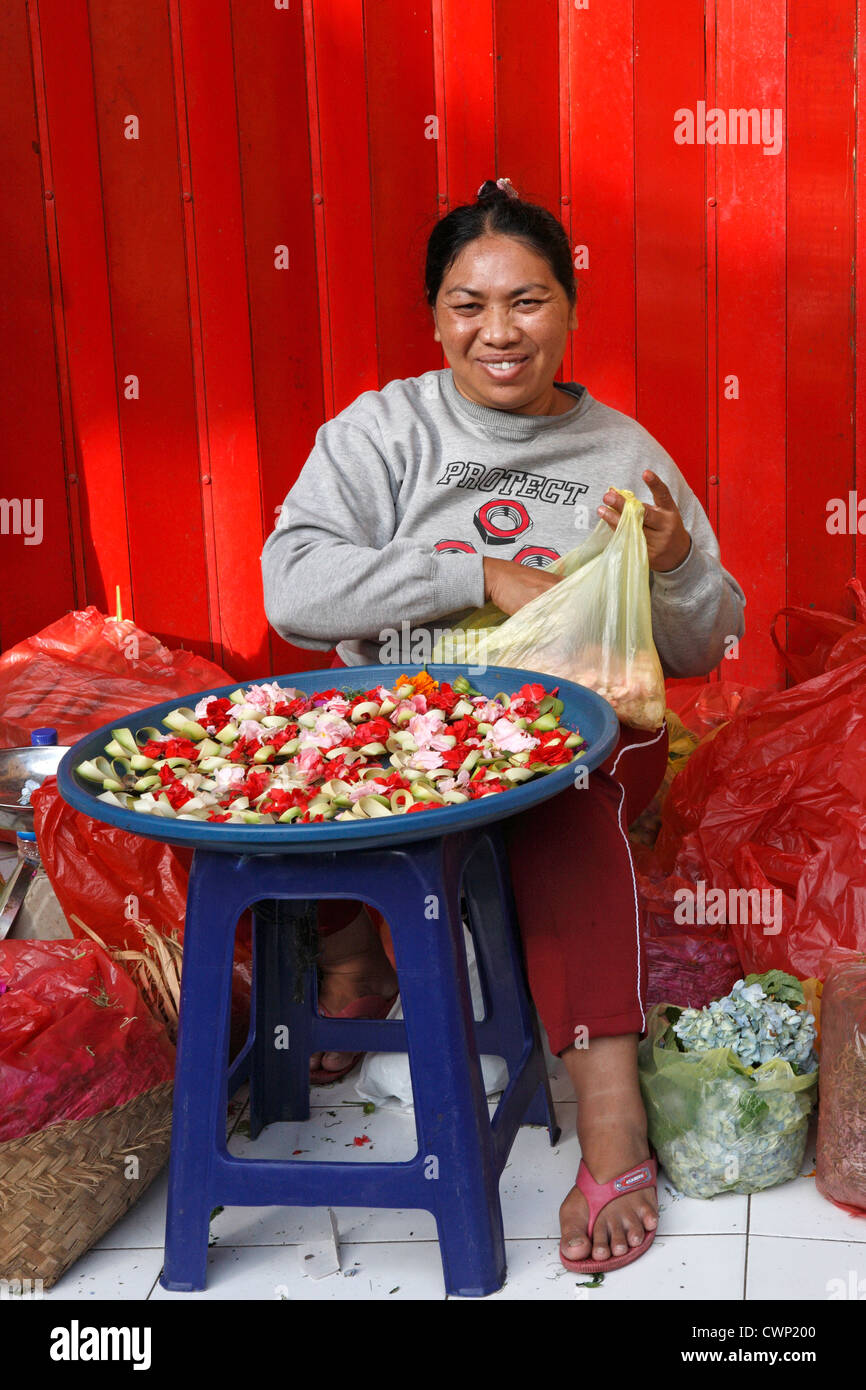 A smiling Balinese woman making offerings which are used as part of the Hindu religion. Ubud Markets, Bali, Indonesia - Stock Image