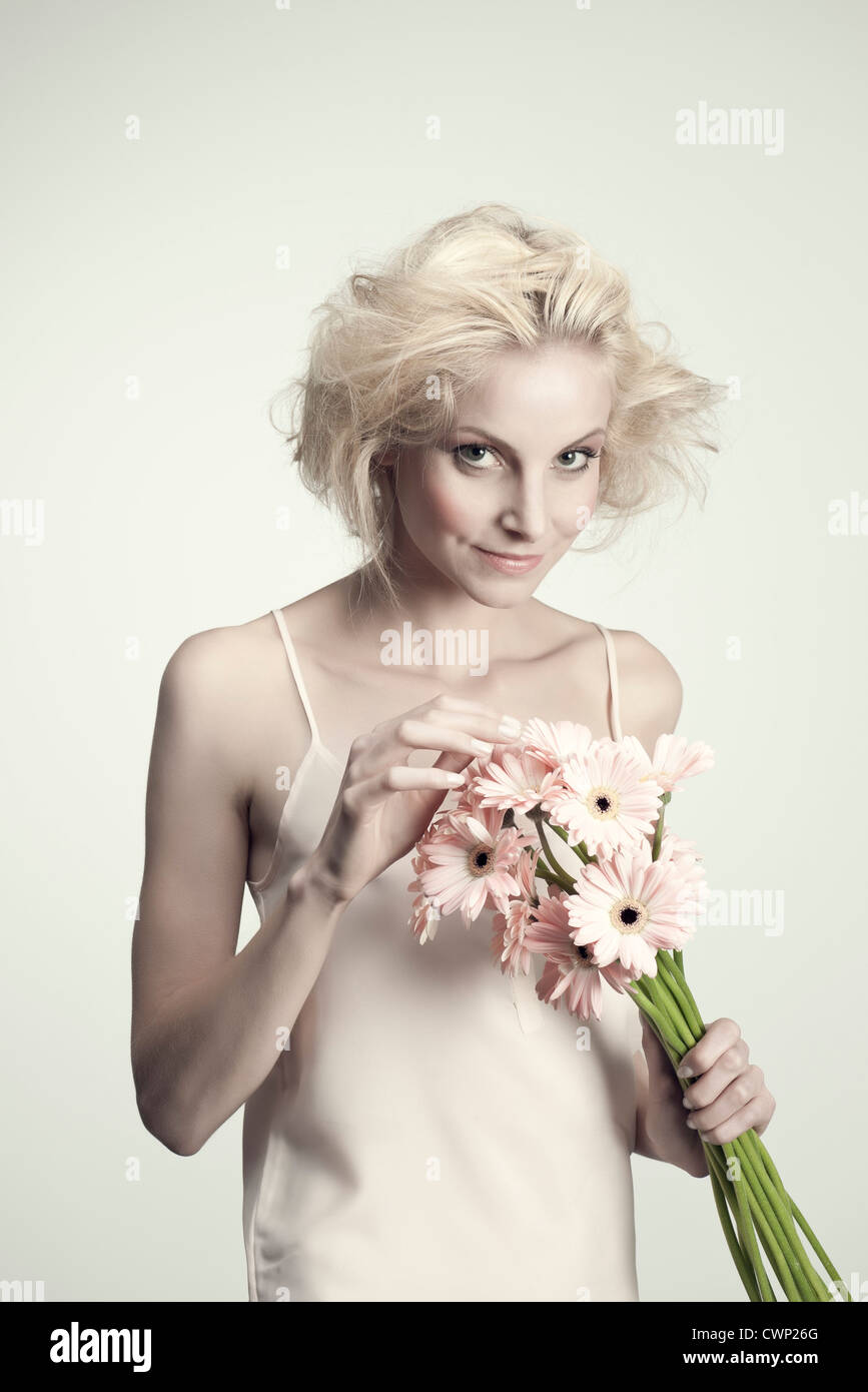 Young woman holding bunch of gerbera daisies - Stock Image