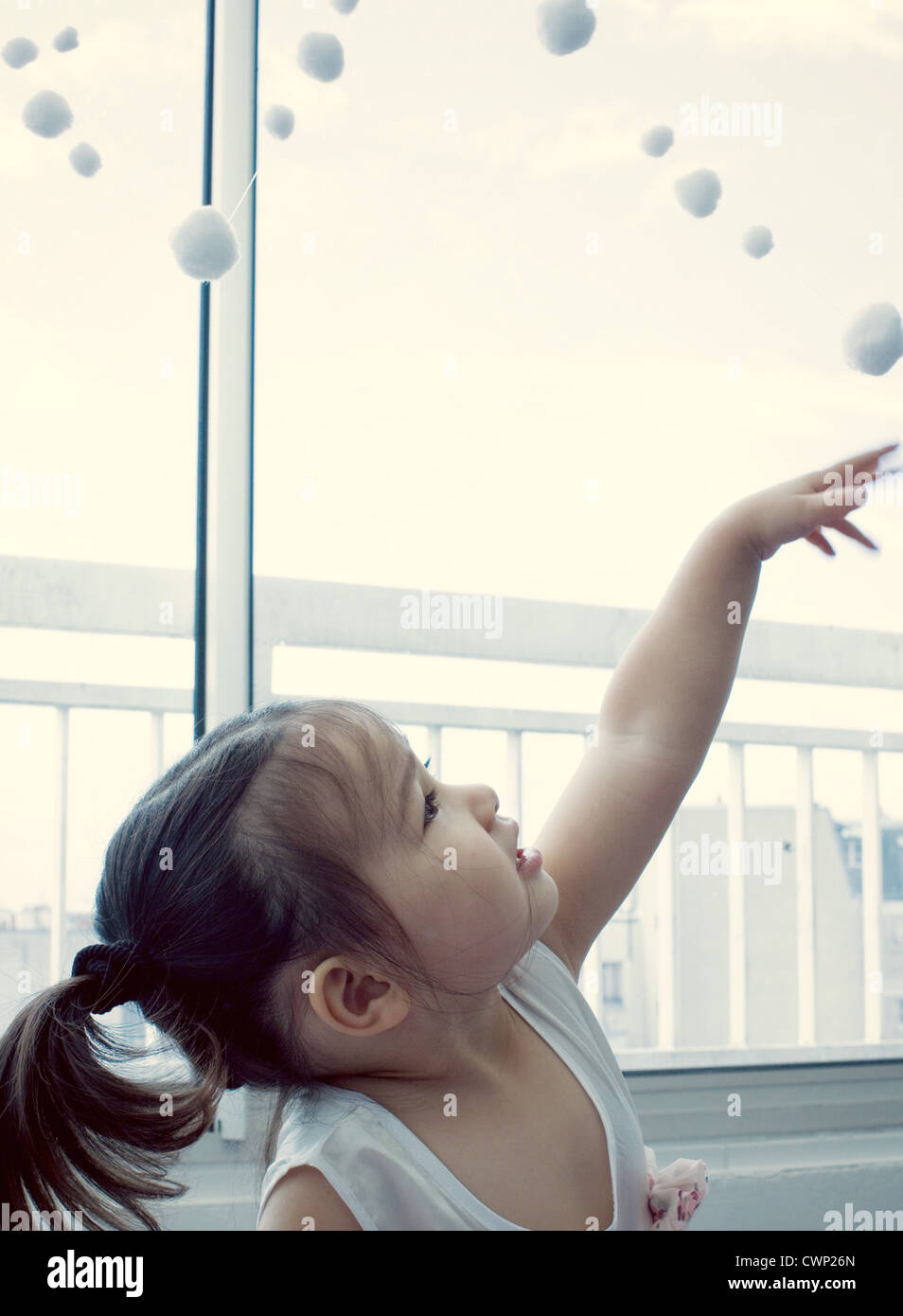 Little girl looking up at pompom garland - Stock Image