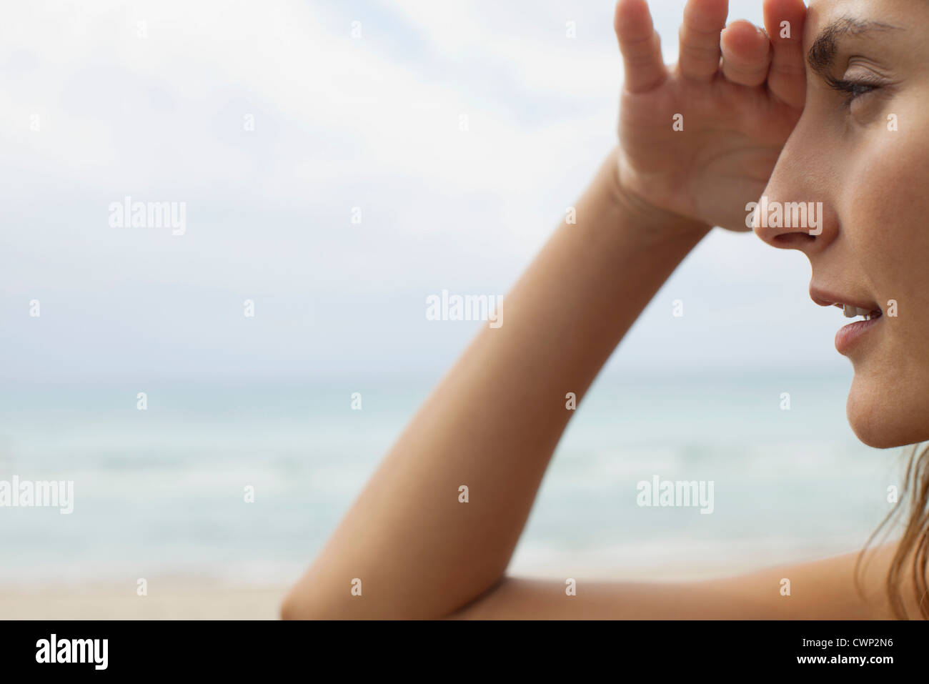 Woman at the beach, shading eyes and looking away - Stock Image