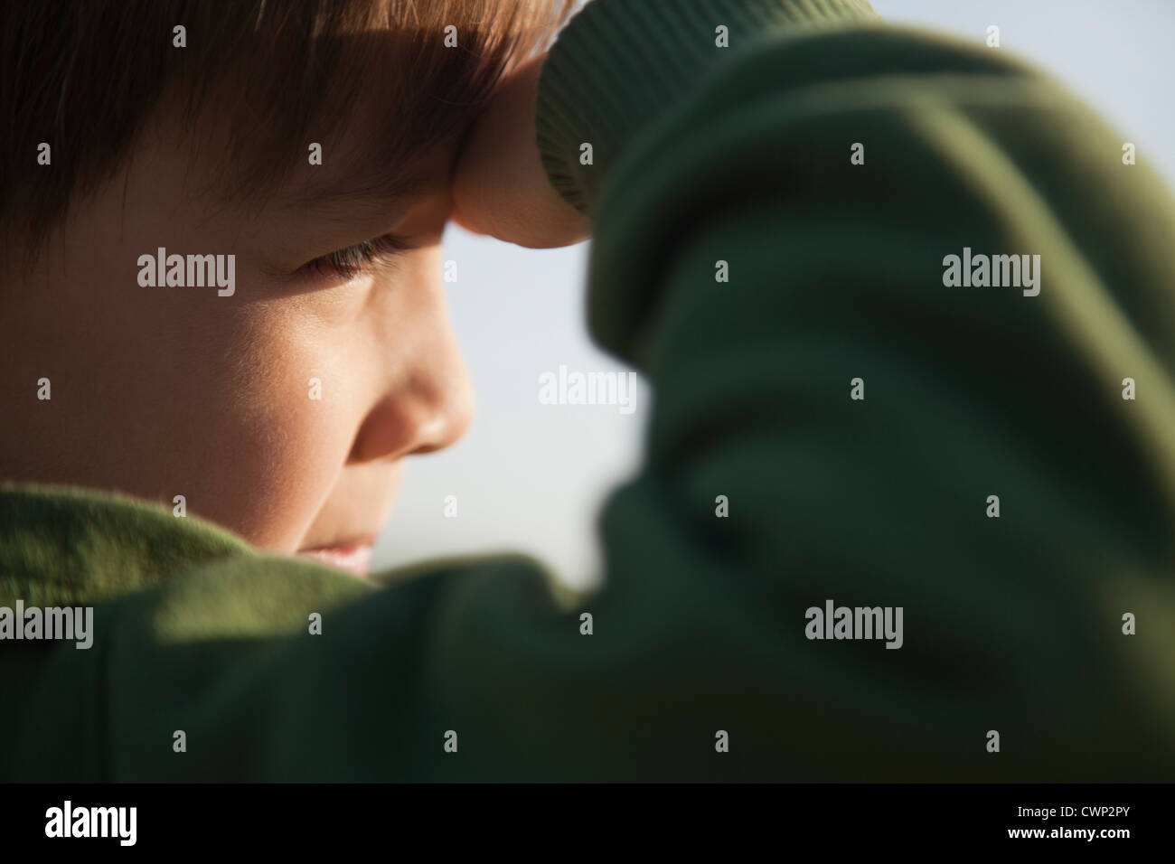 Boy shading eyes, side view Stock Photo