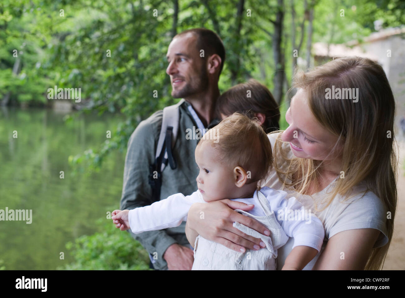 Family in woods, focus on mother holding baby girl - Stock Image
