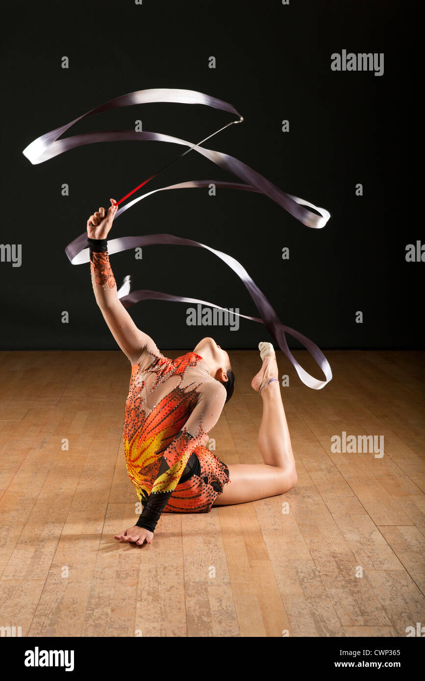 Gymnast bending backwards on floor, twirling ribbon - Stock Image