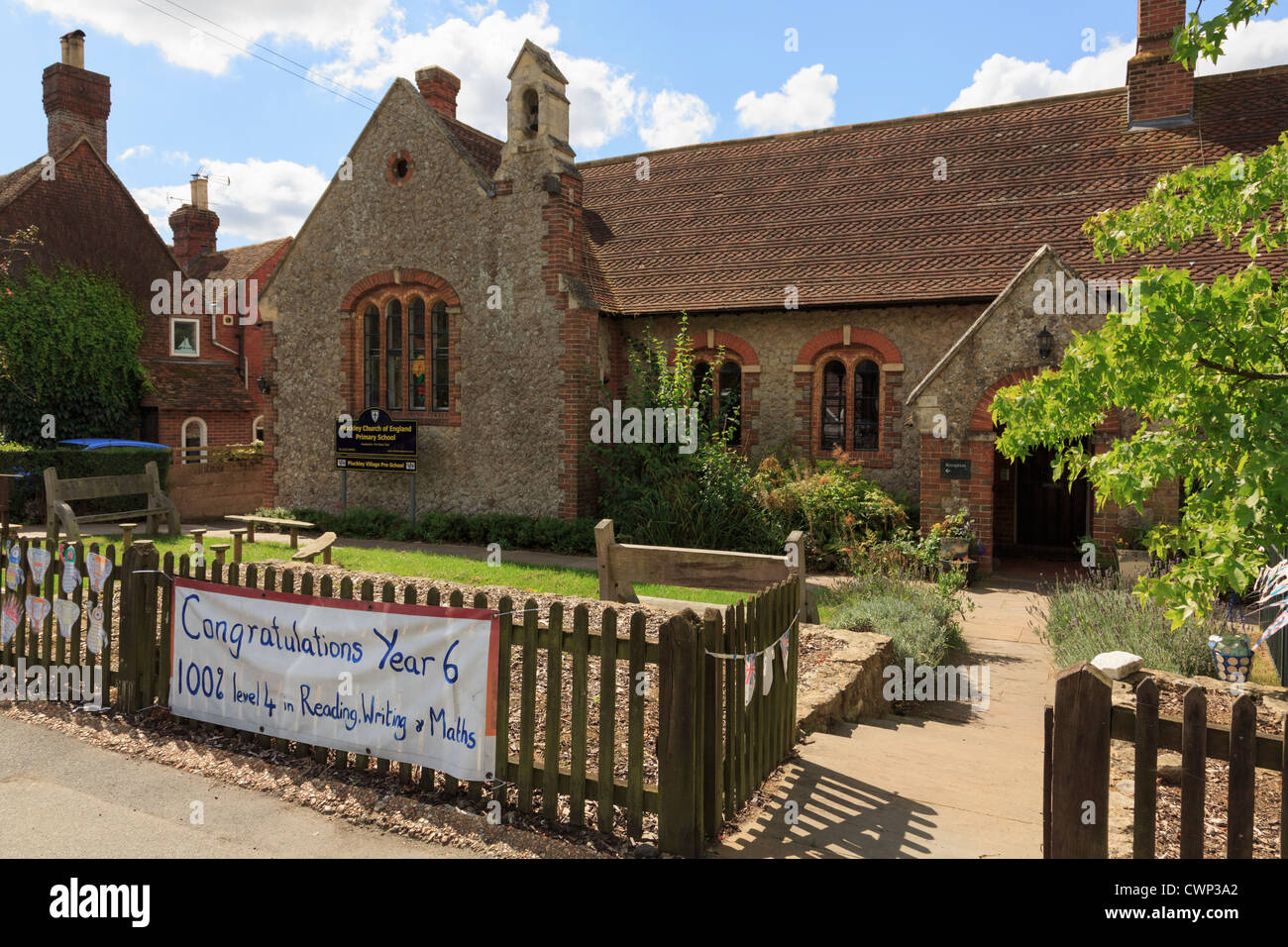 Village Primary School building with sign congratulating year 6 for success in SATS examinations in Pluckley, Kent, - Stock Image