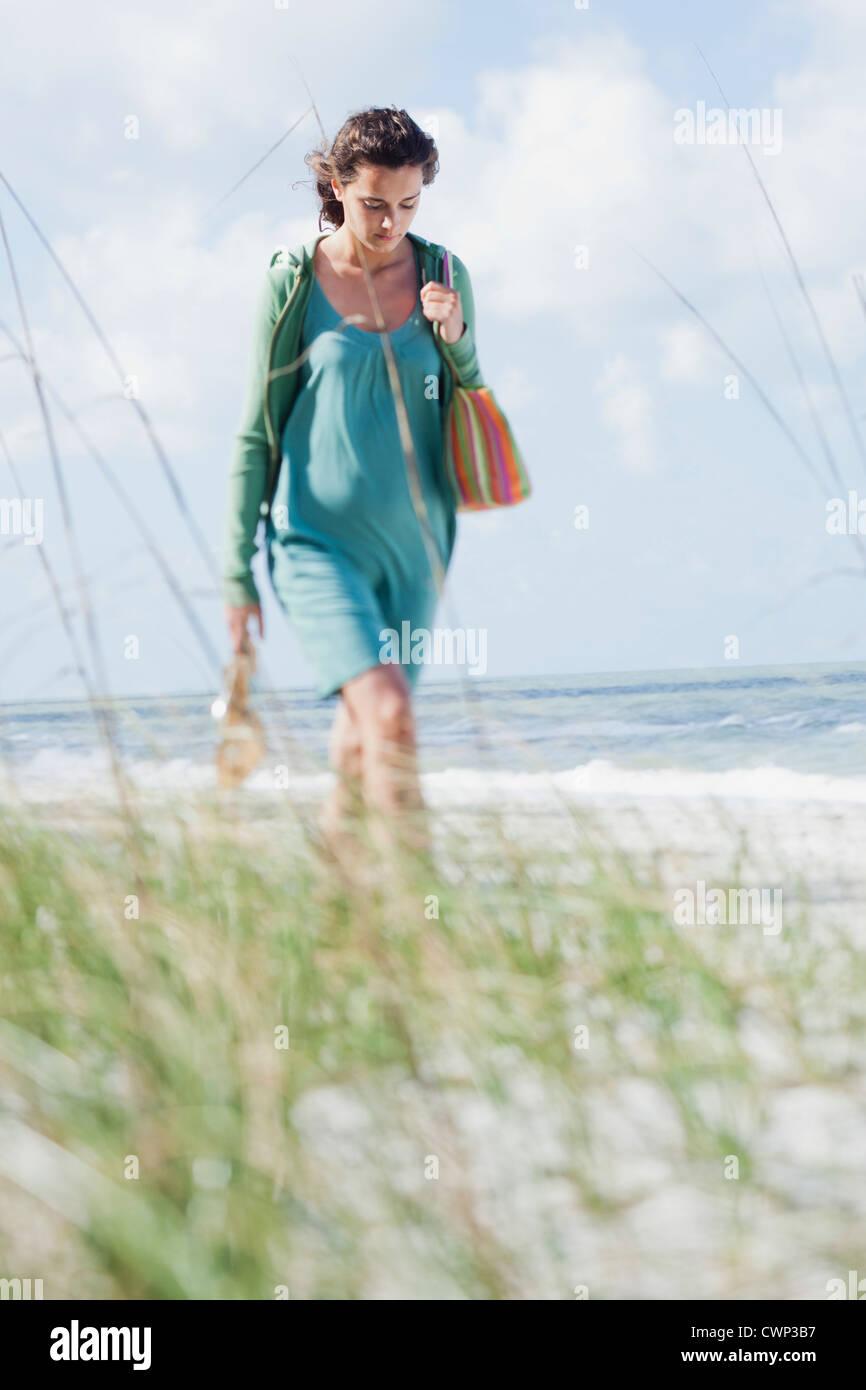 Teenage girl walking on beach - Stock Image