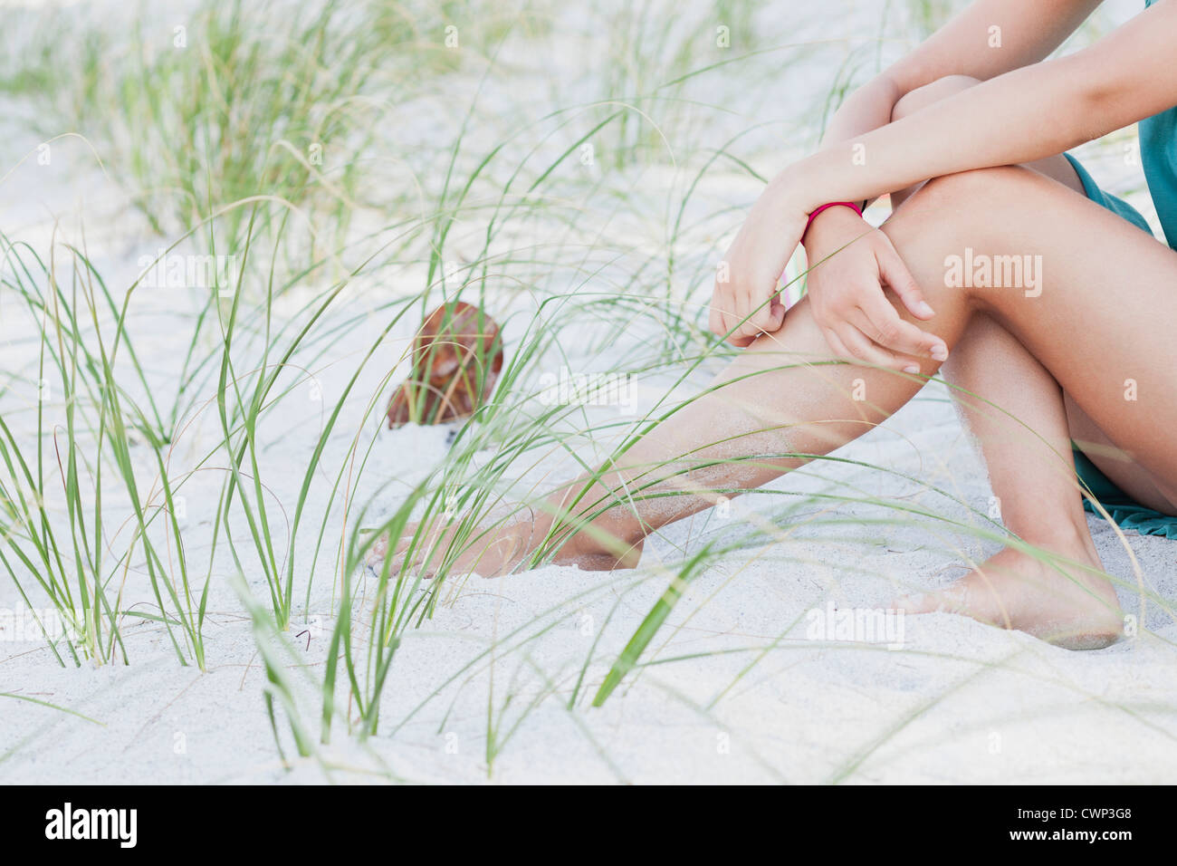 Teenage girl sitting on beach, low section - Stock Image