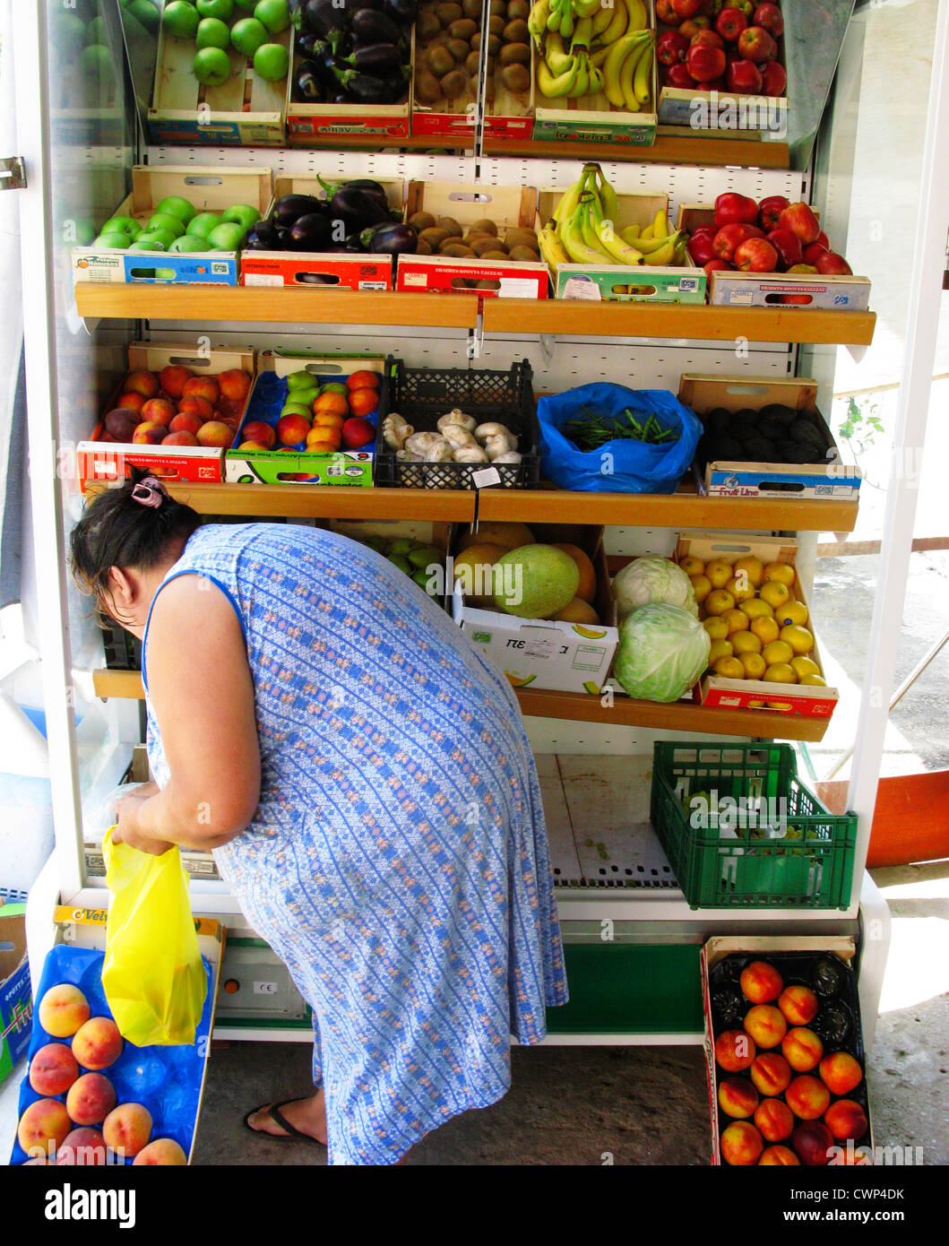 Woman buying fruit from a Greengrocers, Crete, Greece - Stock Image
