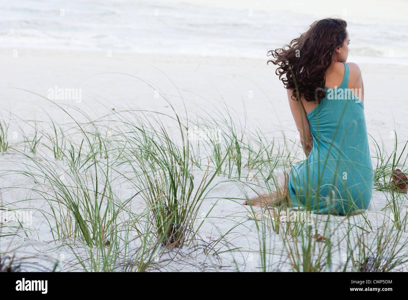 Teenage girl sitting on beach, rear view - Stock Image