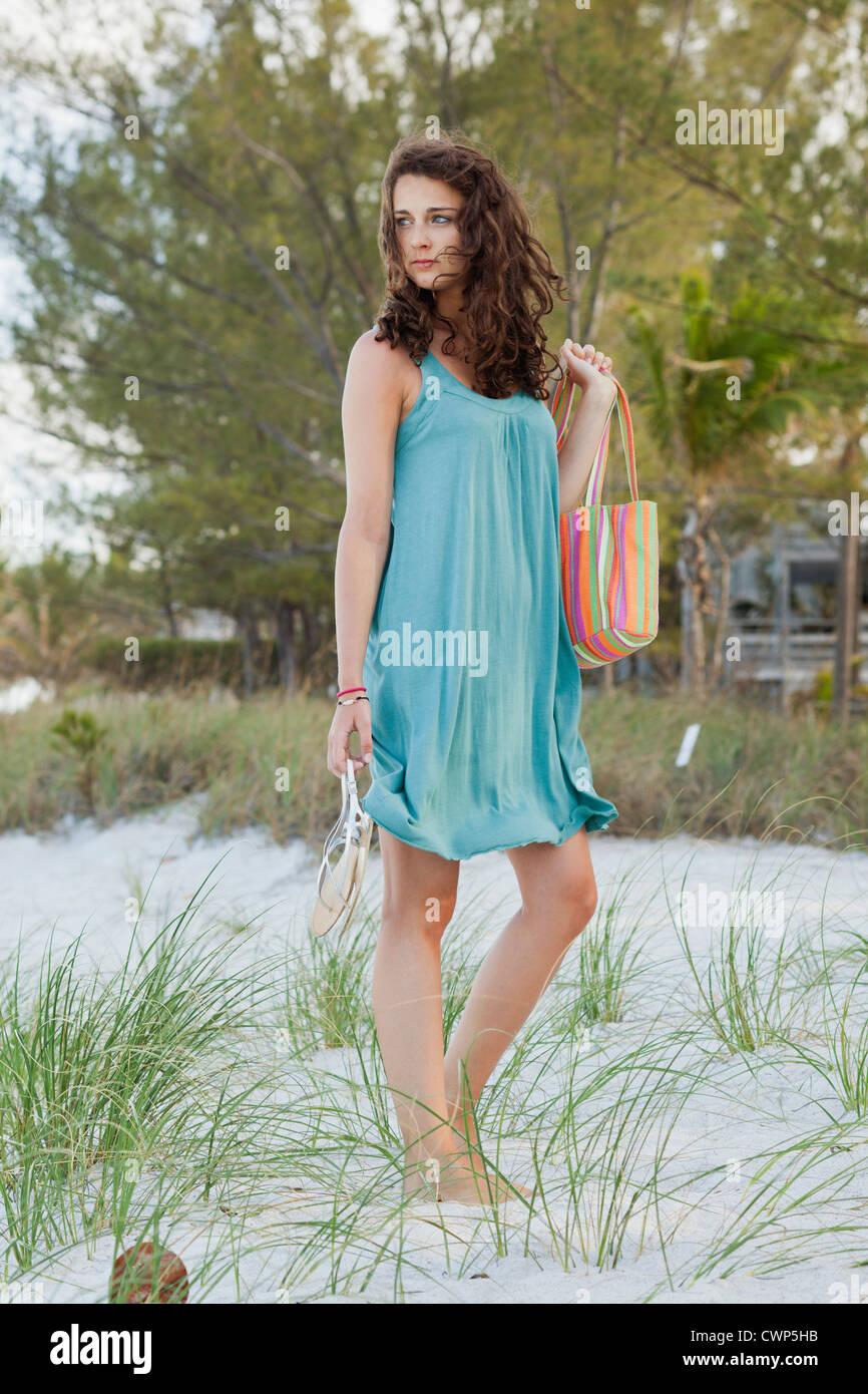 Teenage girl standing on beach - Stock Image