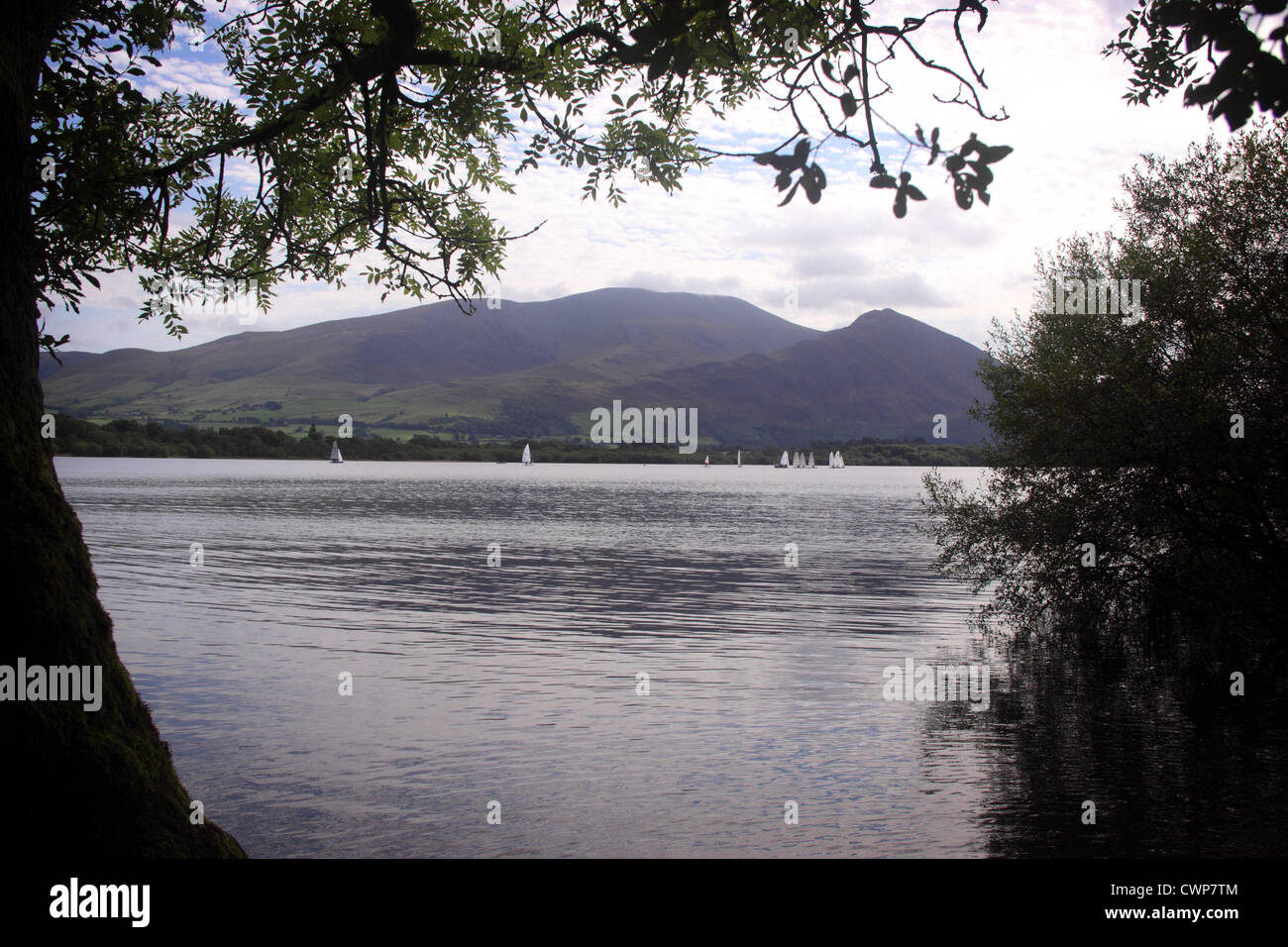 Boats sail on Bassenthwaite lake, looking across from near the Ouse bridge. Lower slopes of Skiddaw rise opposite - Stock Image