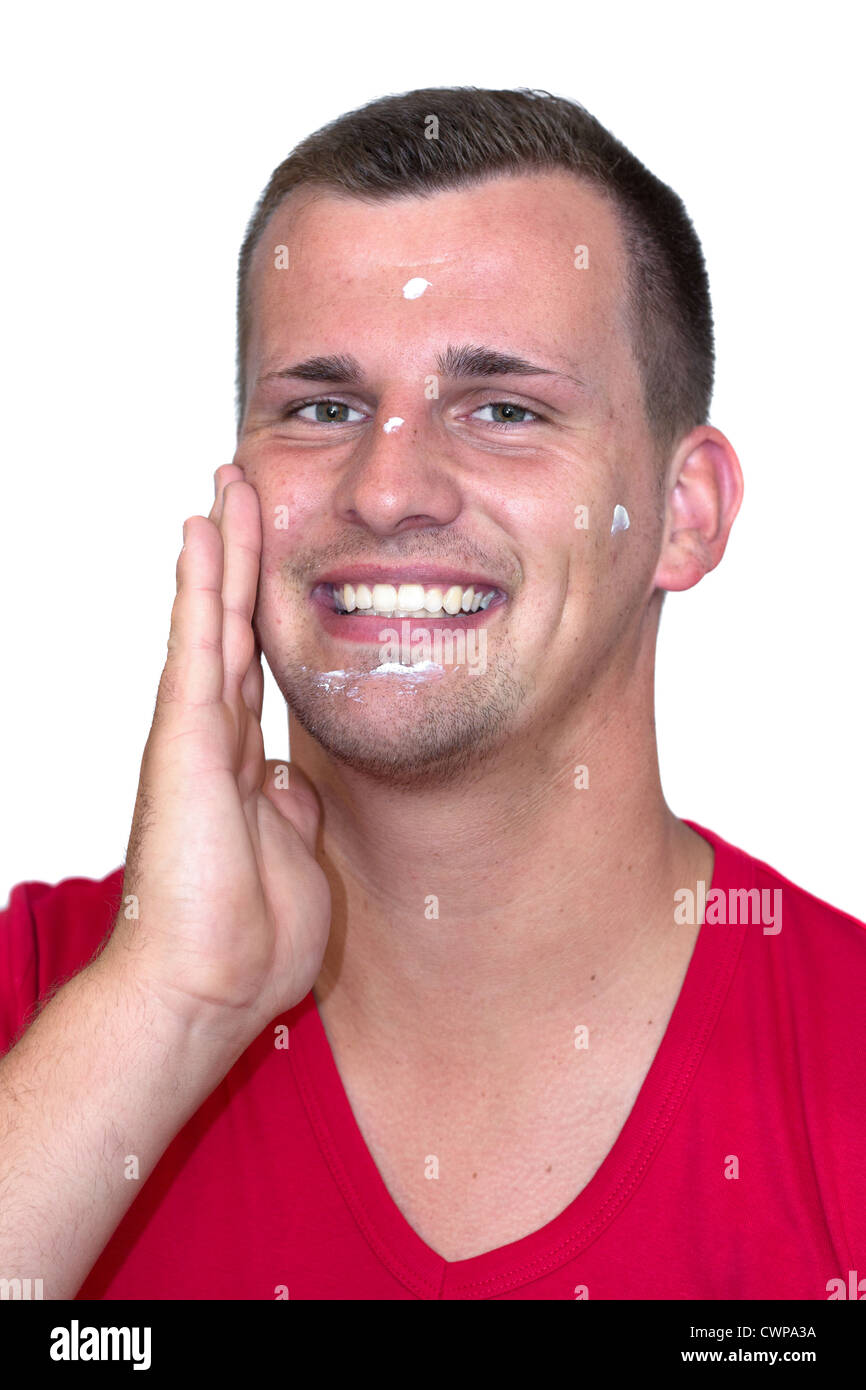 Young white man with moisturizer cream in his face in front of isolated background - Stock Image