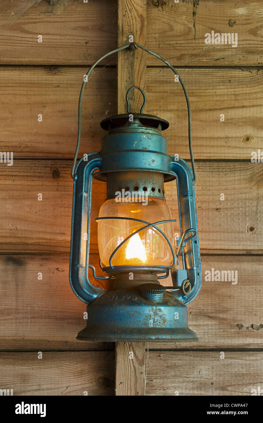 Rusty lit blue lantern hanging in an old shed - Stock Image
