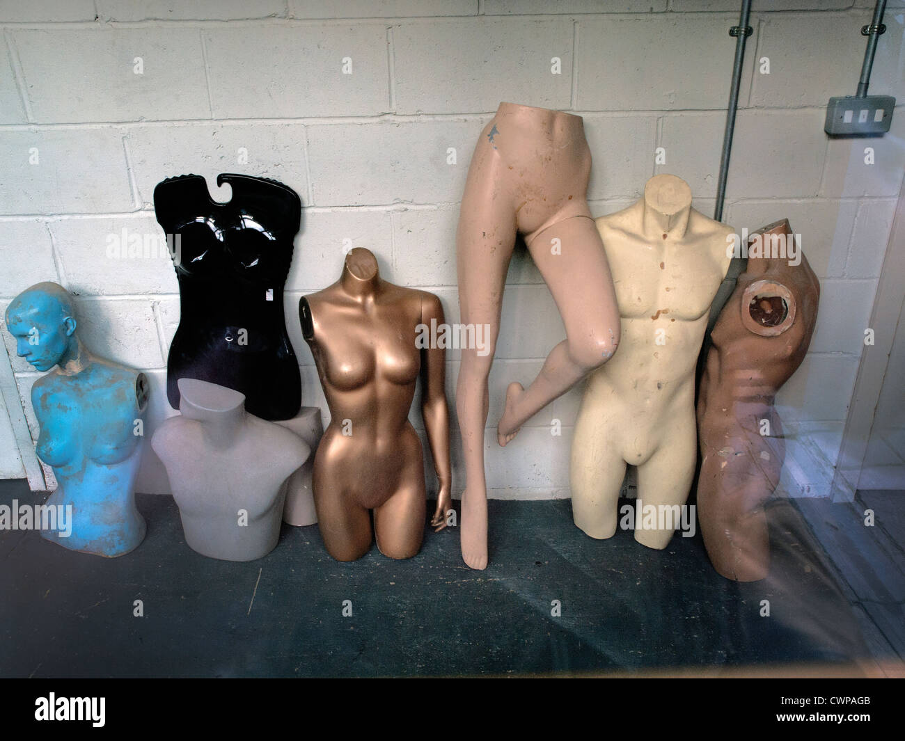 In a shop window stand a variety of mannequin body parts. - Stock Image
