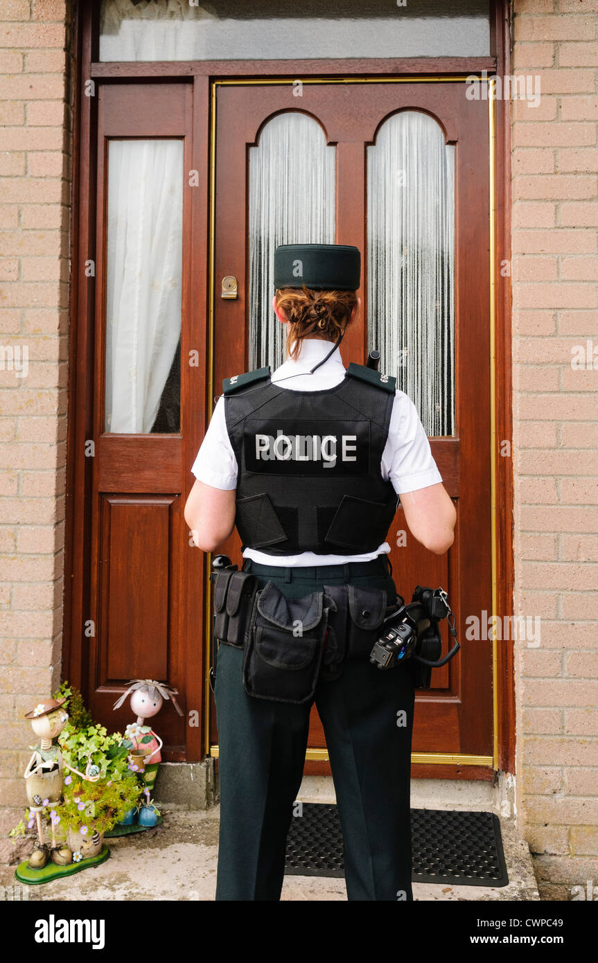 Police woman waits at the front door of a house Stock Photo