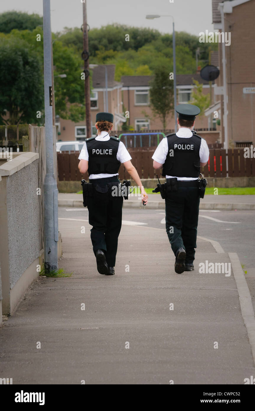 Female and male police officers walking along the footpath of a street in a residential area (vignetted) - Stock Image