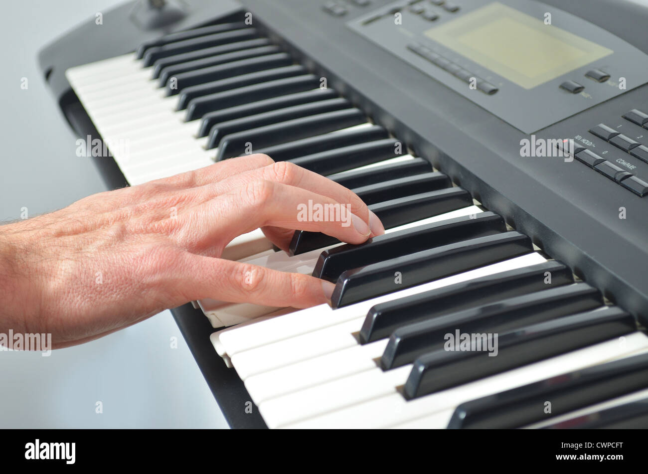 Single hand on electronic synthesizer playing music - Stock Image