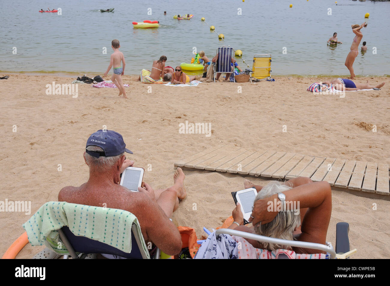 a couple of tourists reading electronic book  ebook on the beach - Stock Image