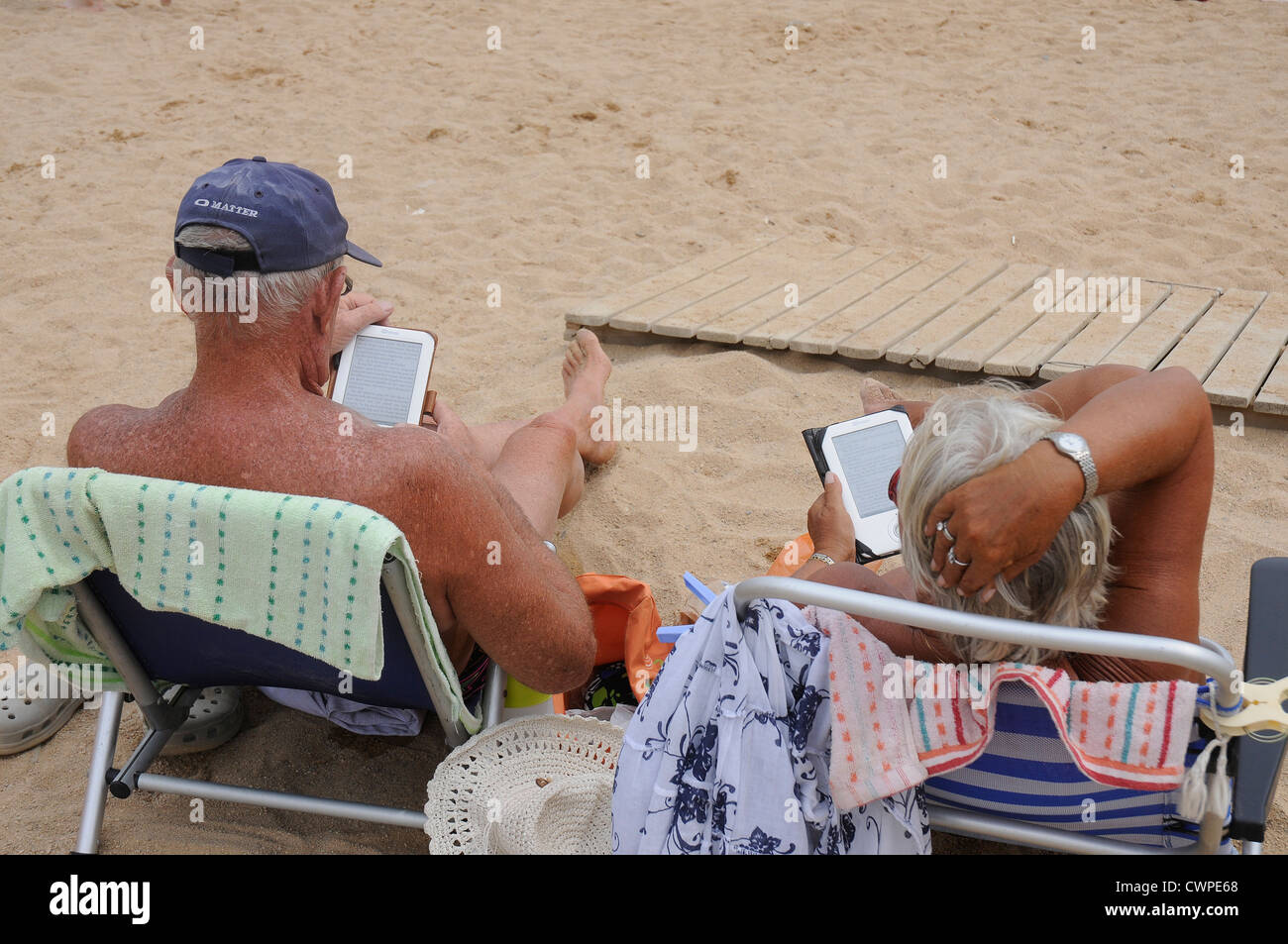 old couple tourists reading electronic book  ebook on the beach - Stock Image