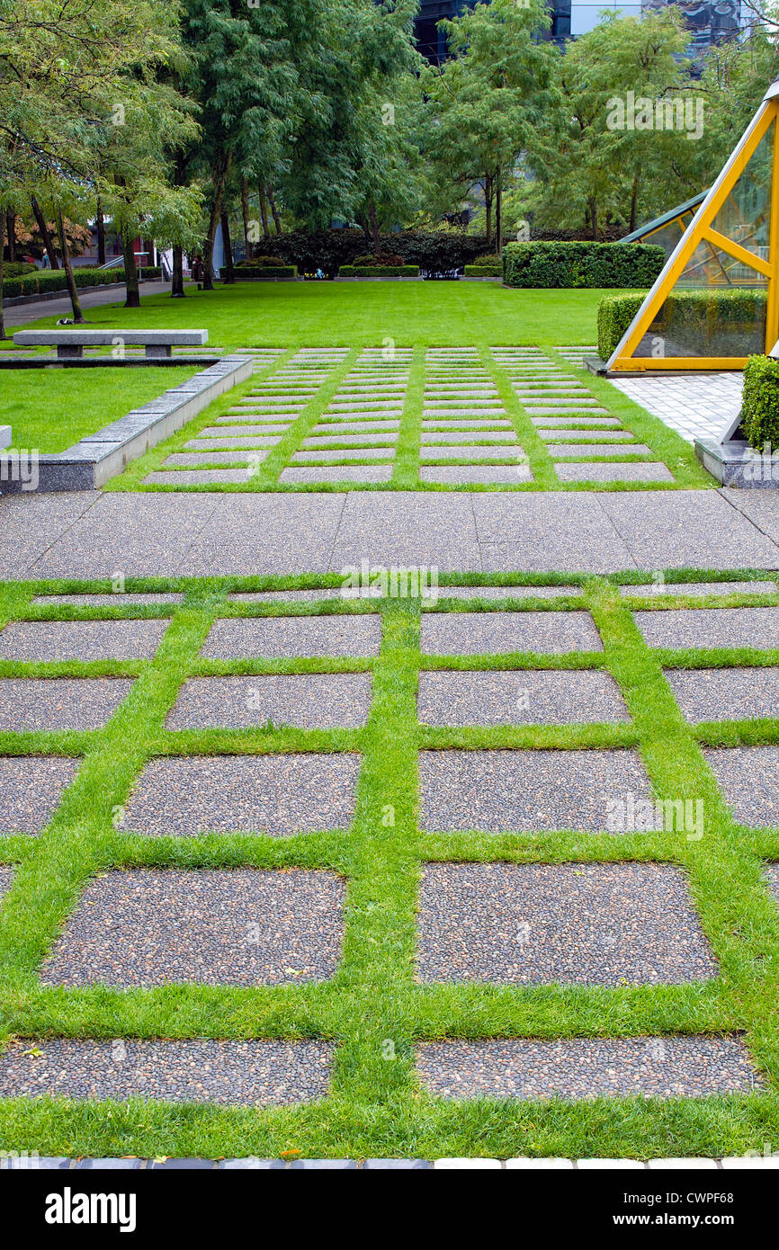 Grass Growing Between Concrete Pavers in Public Parks Landscaping - Stock Image