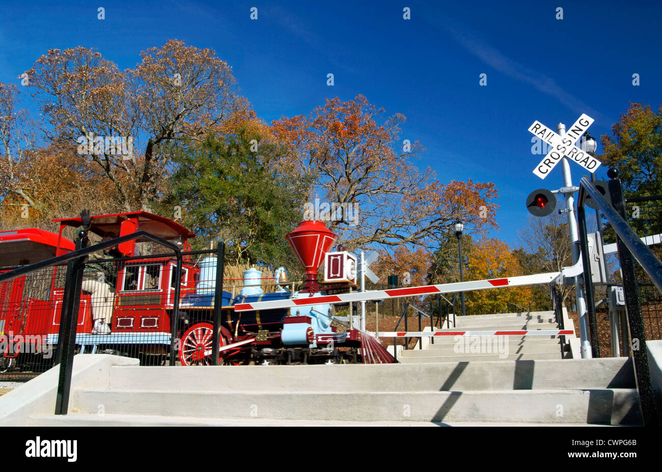 Raleigh, NC, North Carolina. Miniature train in Pullen park at railroad crossing. - Stock Image