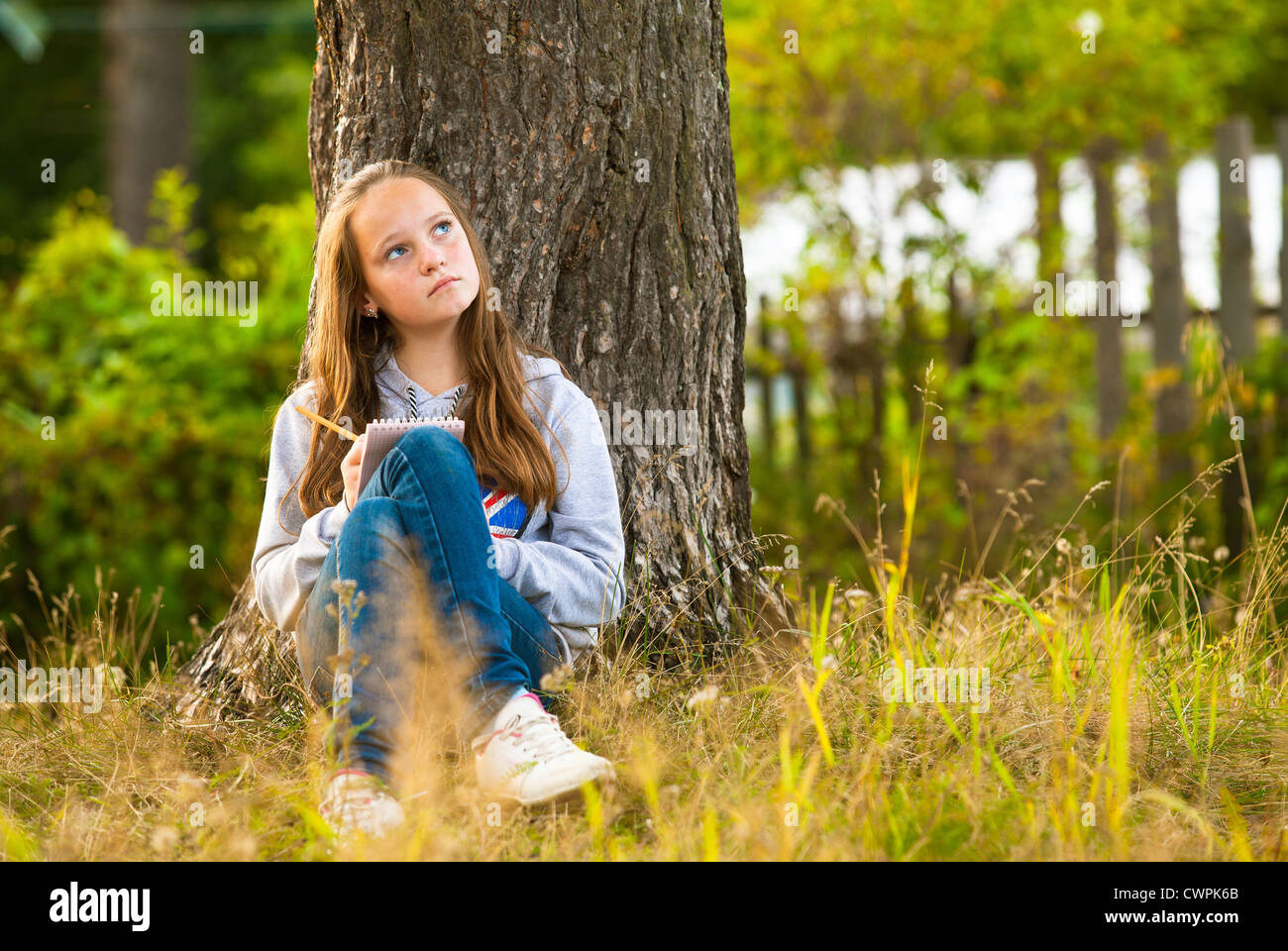 Beautiful teen-girl writing in a notebook while sitting in the park (dreamily looks up) Stock Photo